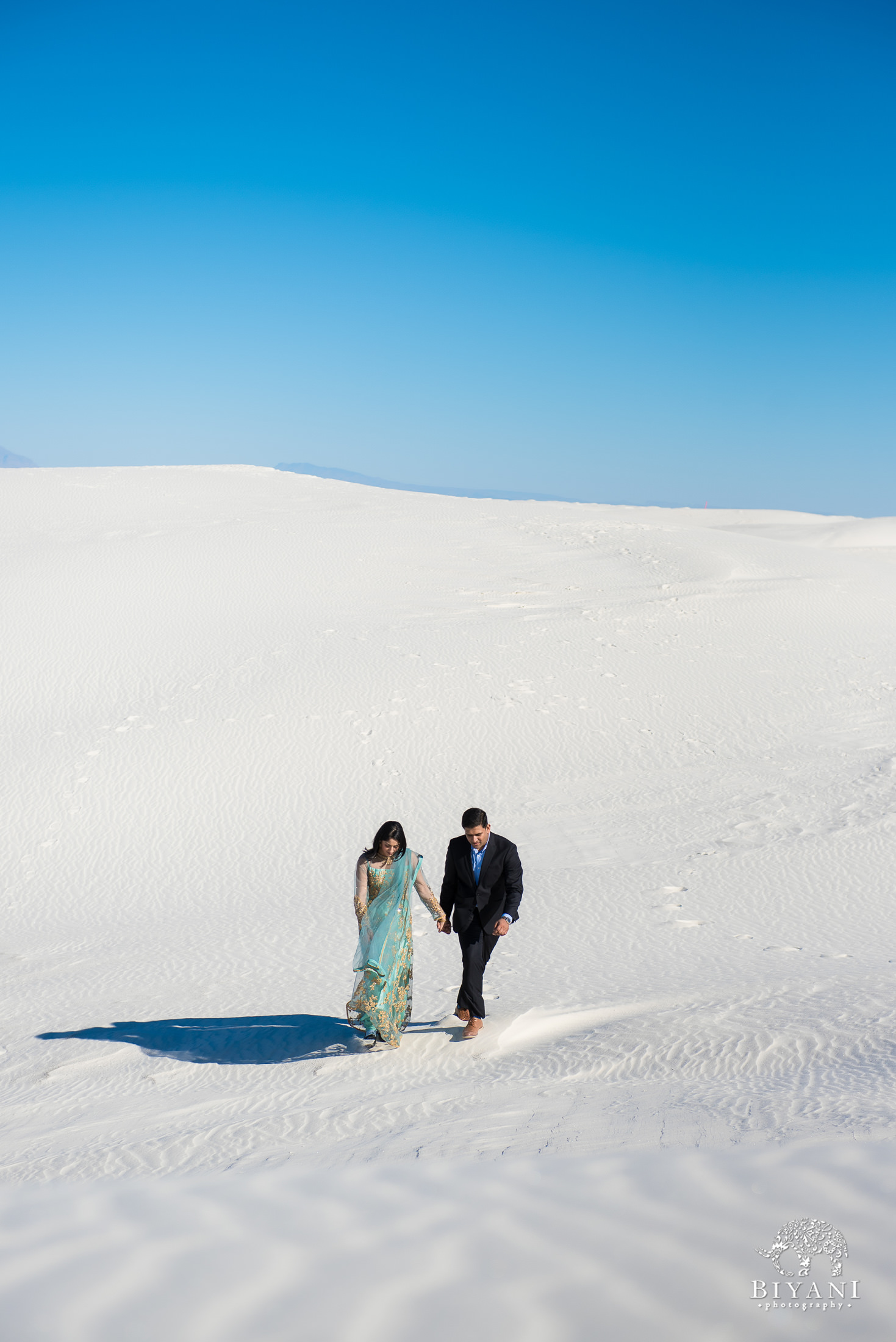 couple walk hand in hand down steep sand dunes in New Mexico