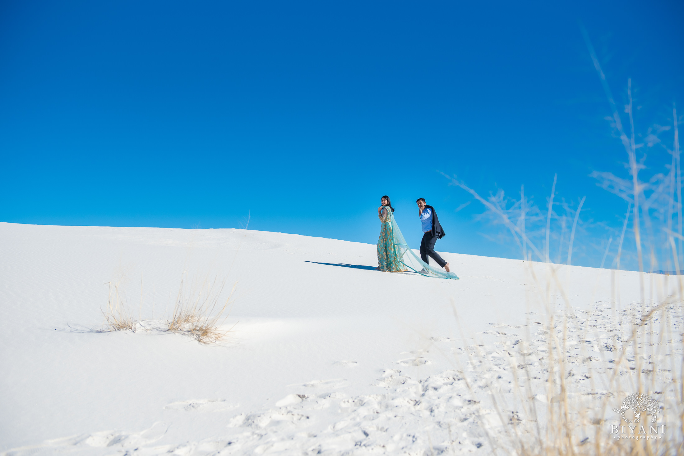 couple walks up a sand dune together dressed in traditional Indian dress