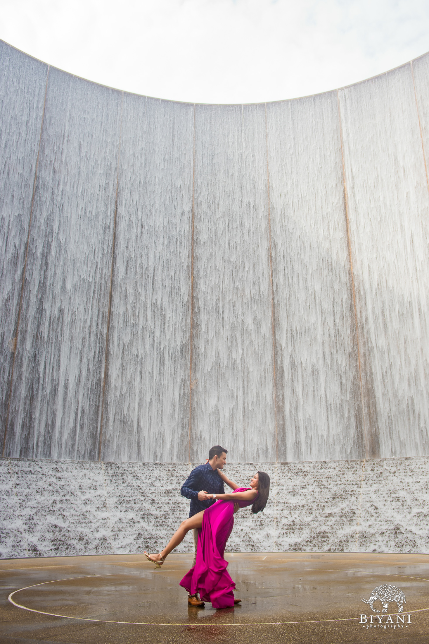 Engagement photos of couple dipping at the Houston Galleria Water Wall