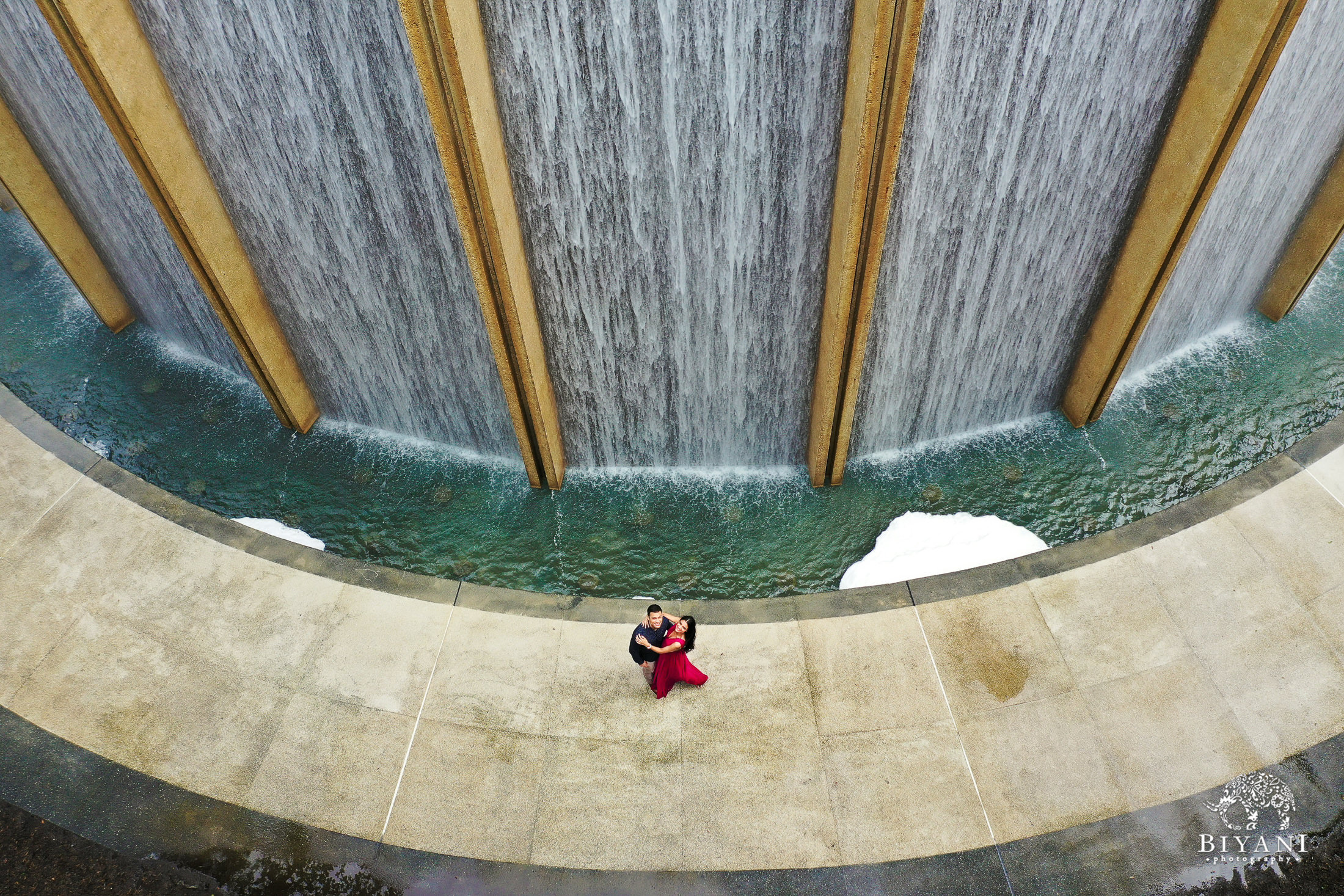 Ariel footage of couple posing in front of Water Wall at Houston Galleria