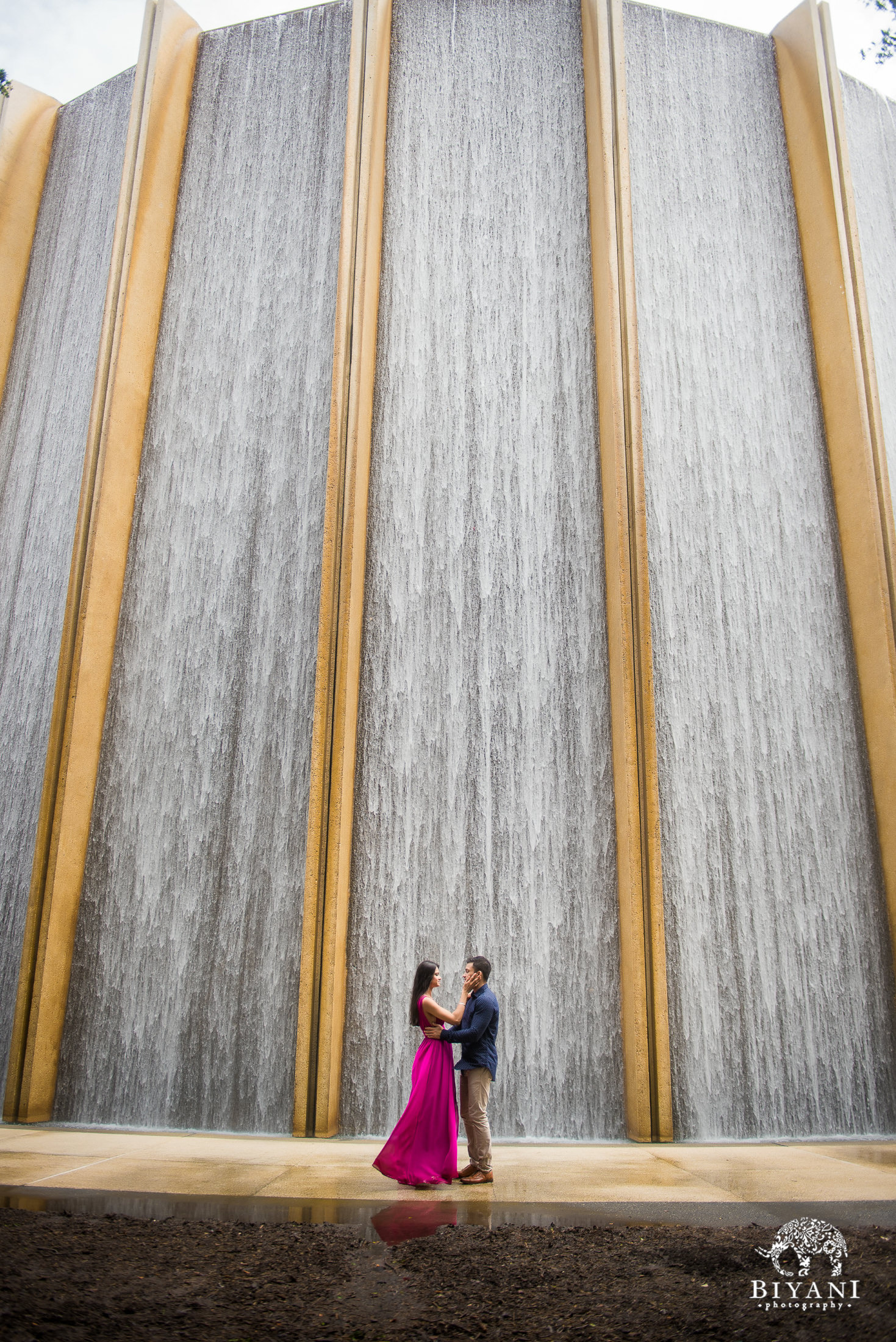 Long distance shot of couple during engagement shoot at water wall Houston Galleria