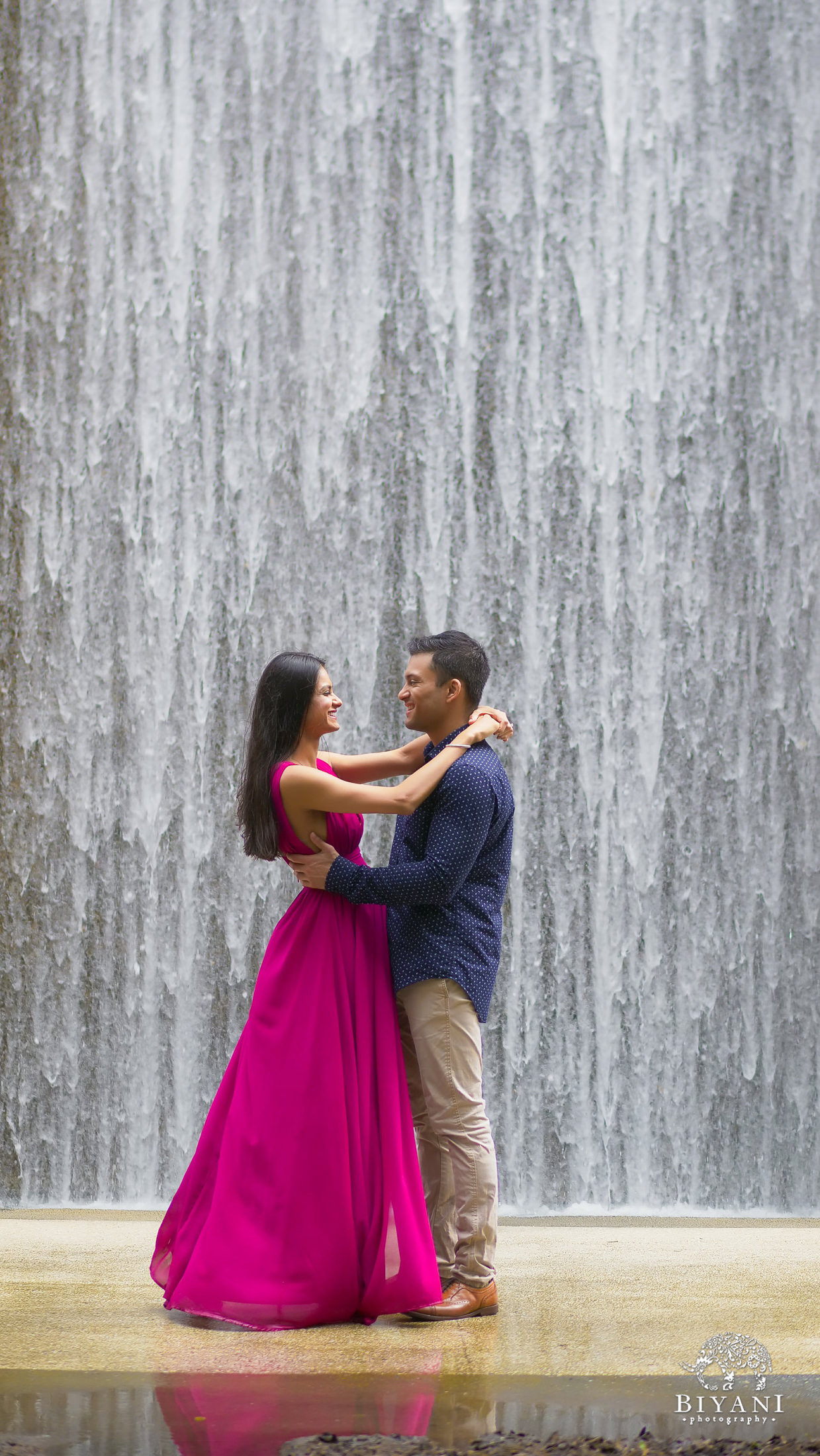 couple standing close together to pose for engagement photos in front of Houston Galleria Water Wall