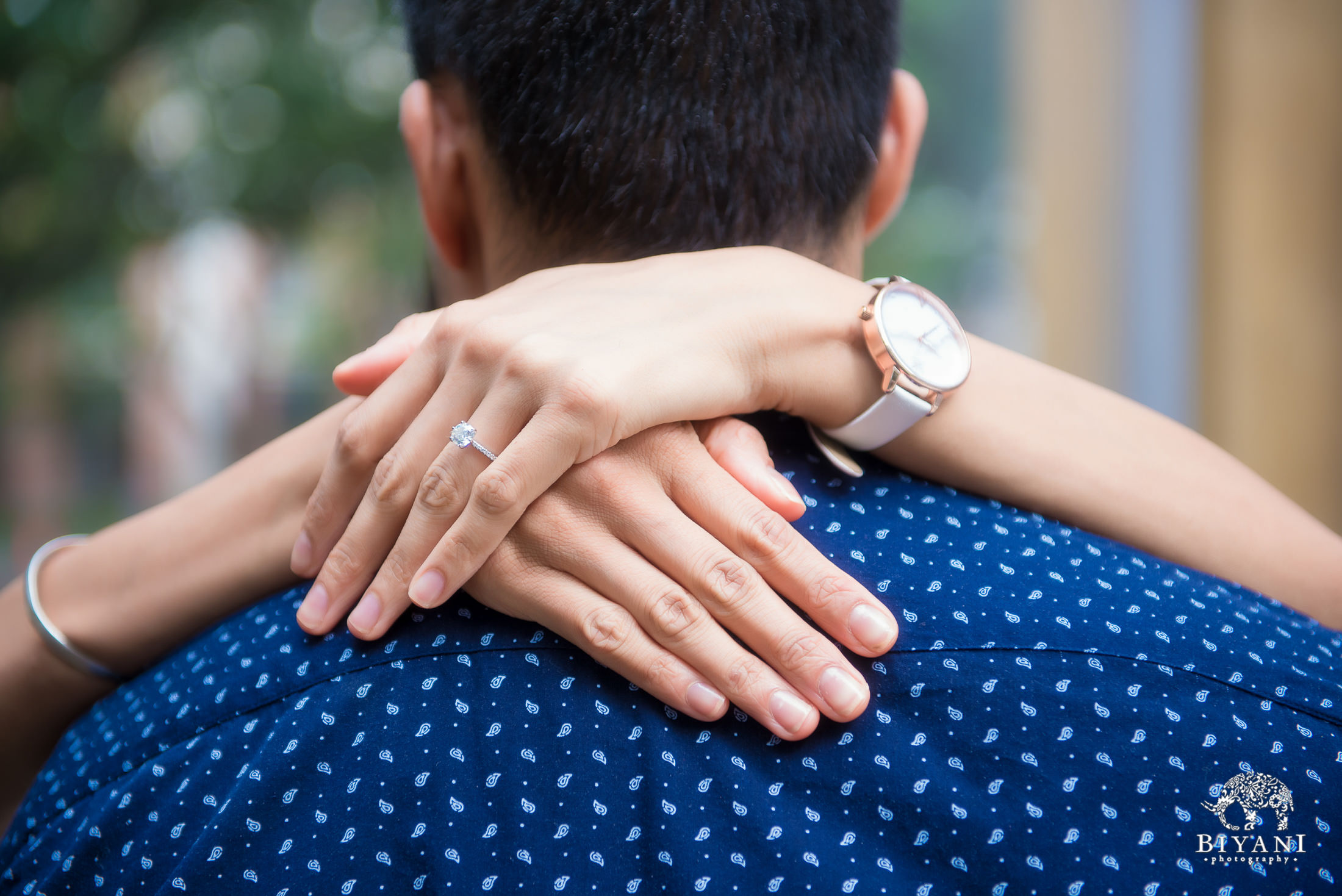 bride's hands wrapped around groom's shoulders during engagement photo shoot in Houston