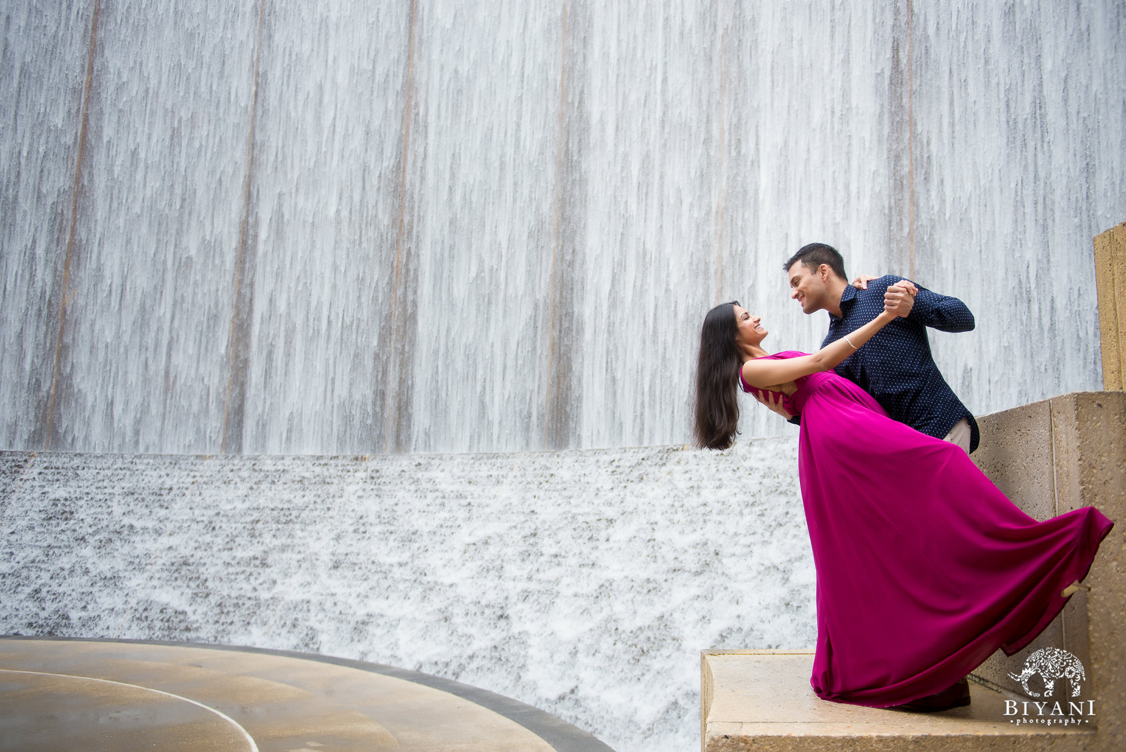 groom dipping bride over the water wall at Houston Galleria