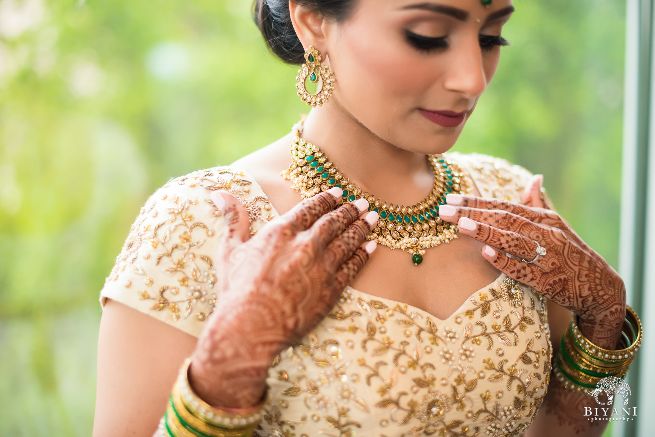 Indian bride putting on her necklace before her wedding ceremony