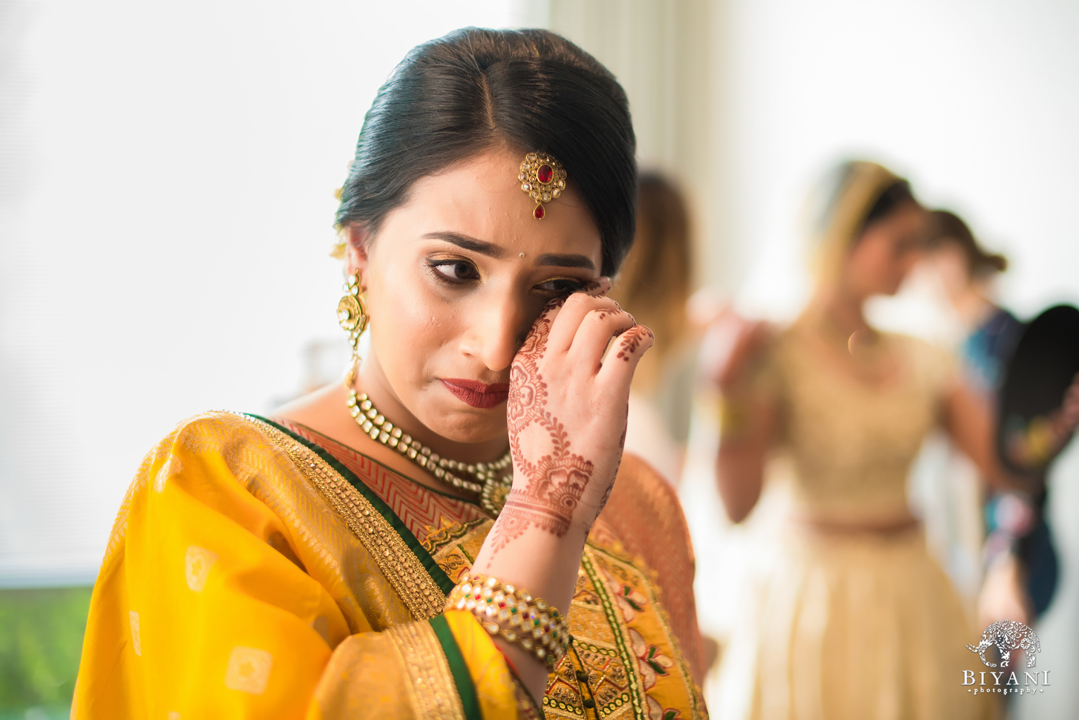Sister of the bride crying while watching her sister get ready for her ceremony