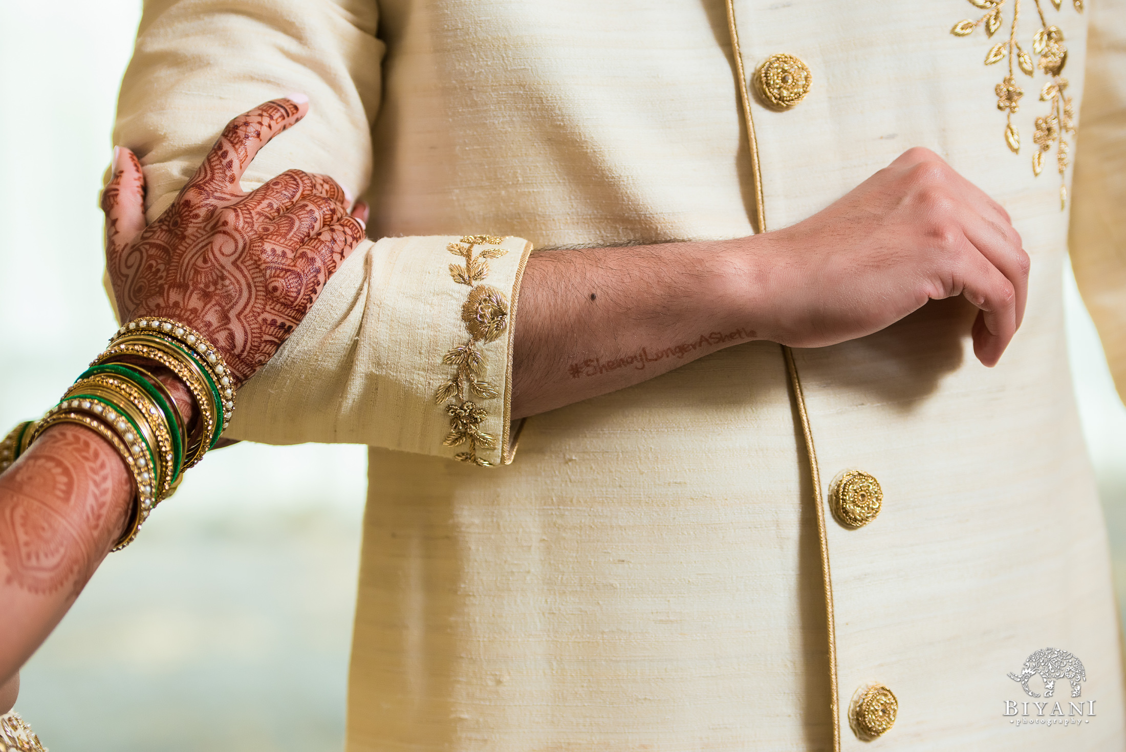 bride resting her hand on groom's arm during couple portraits