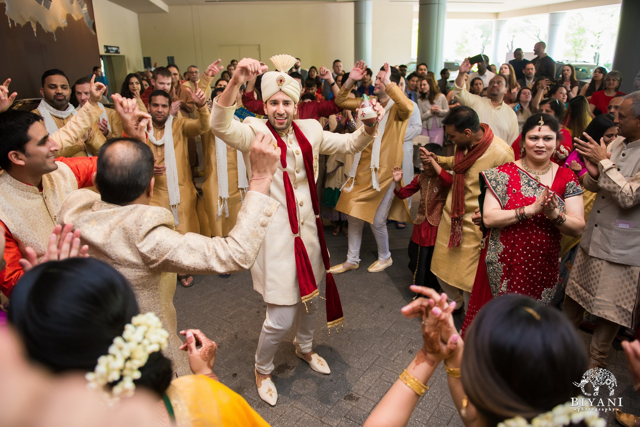 groom raising arms during baraat