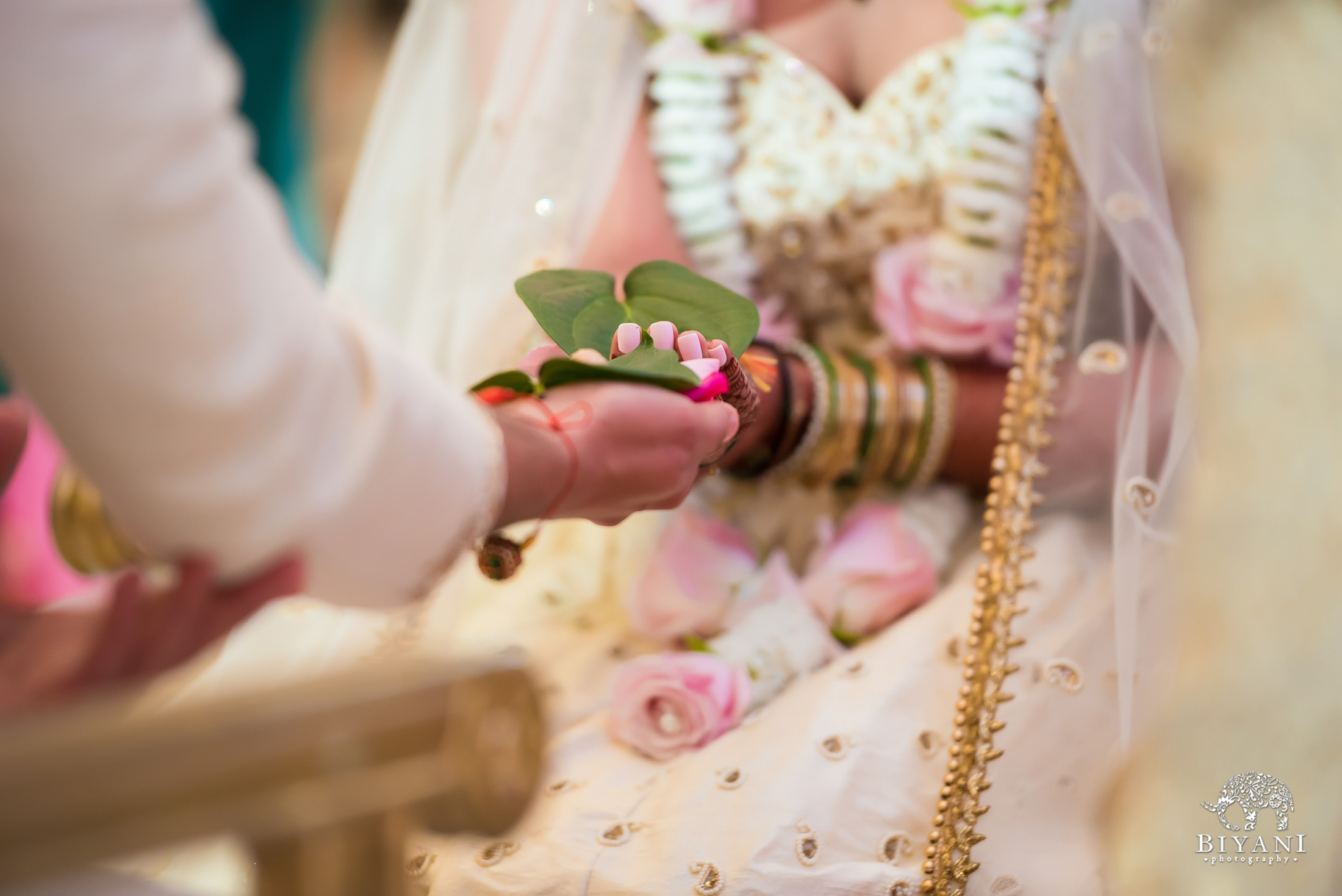 Bride and groom during wedding ceremony holding leaves