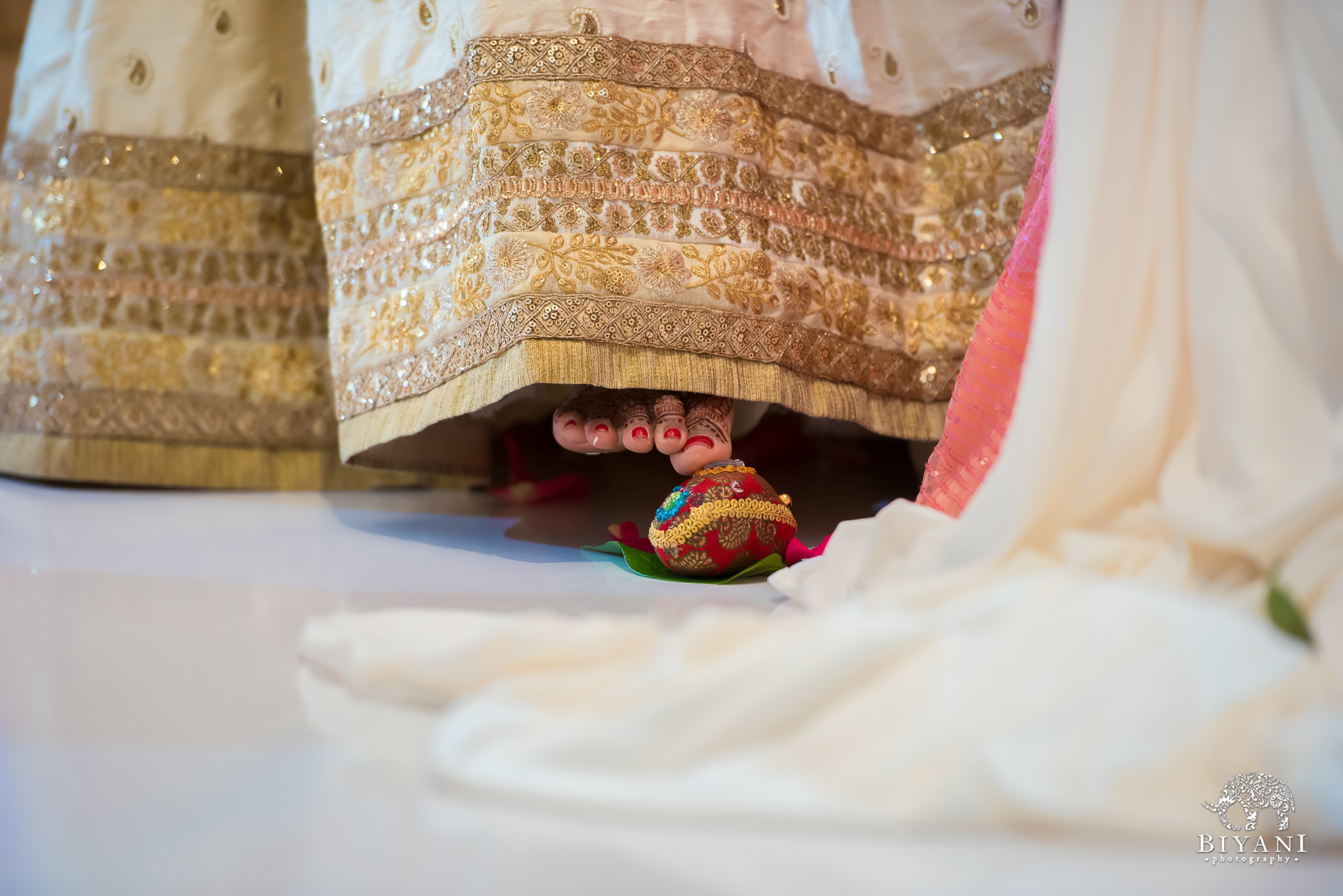 Bride touching the pot with her toes during Indian wedding ceremony to signify the commitments to her husband