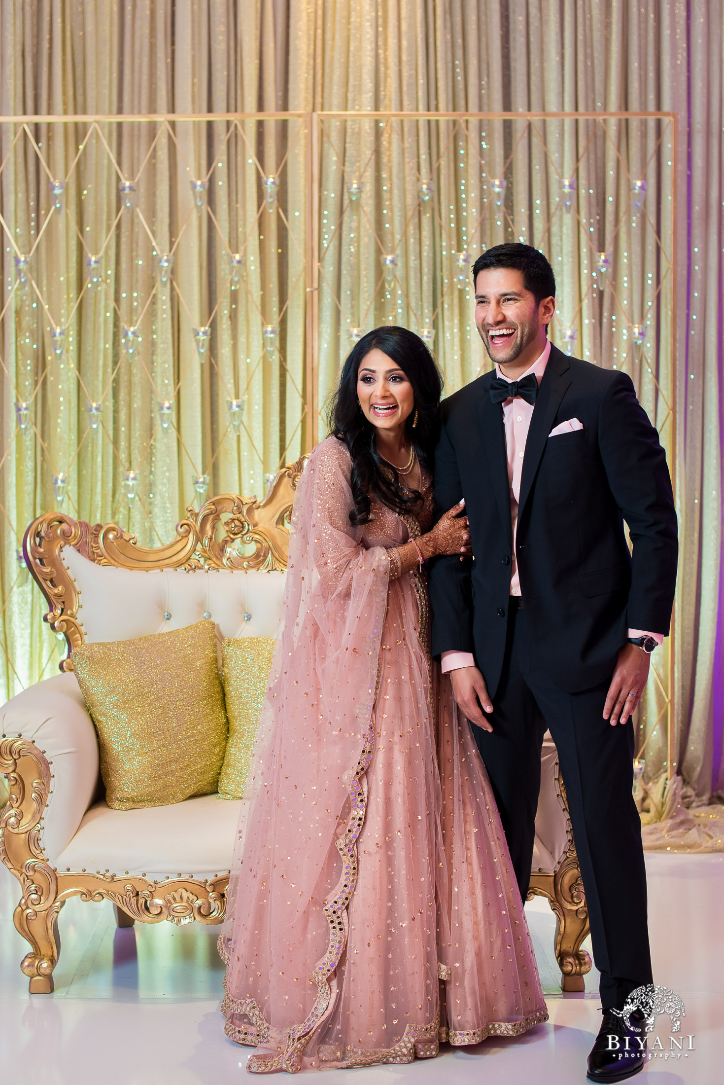 Indian couple laughing into the distance in reception dress