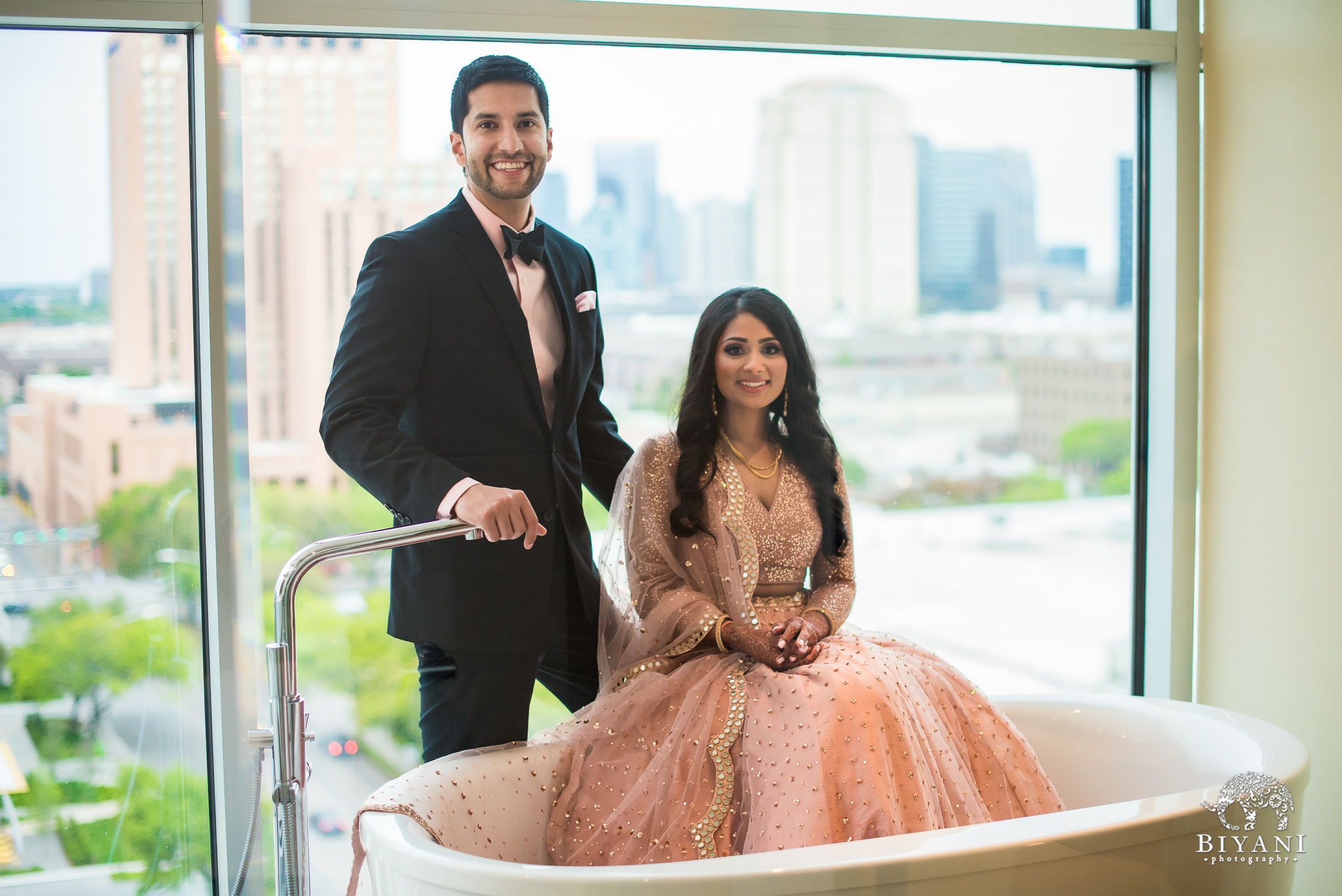 couple poses in bathtub in reception outfits