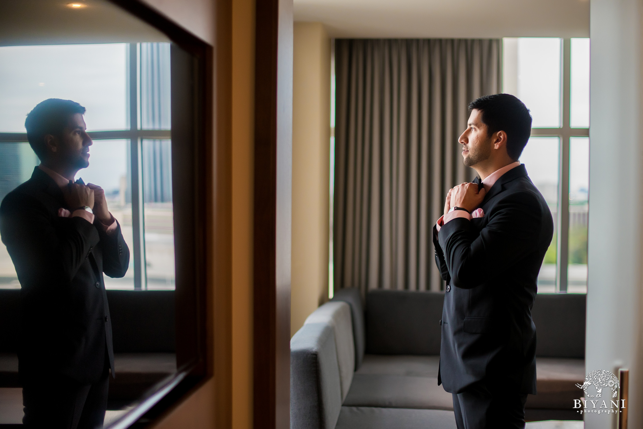 Groom adjusting his tie while looking out the window of the Hyatt Regency at the Galleria Houston