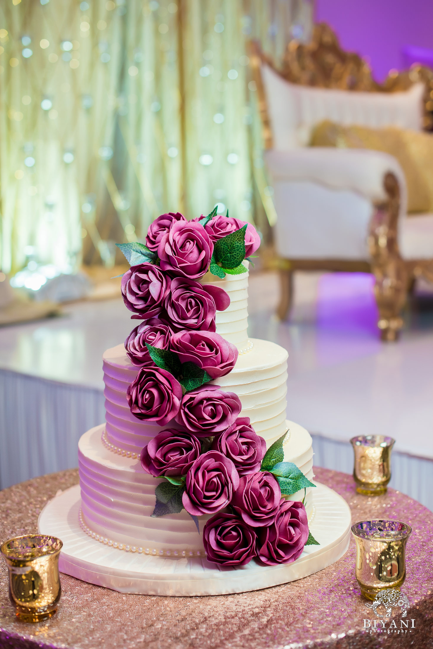 cake decorated with pink icing roses at the reception