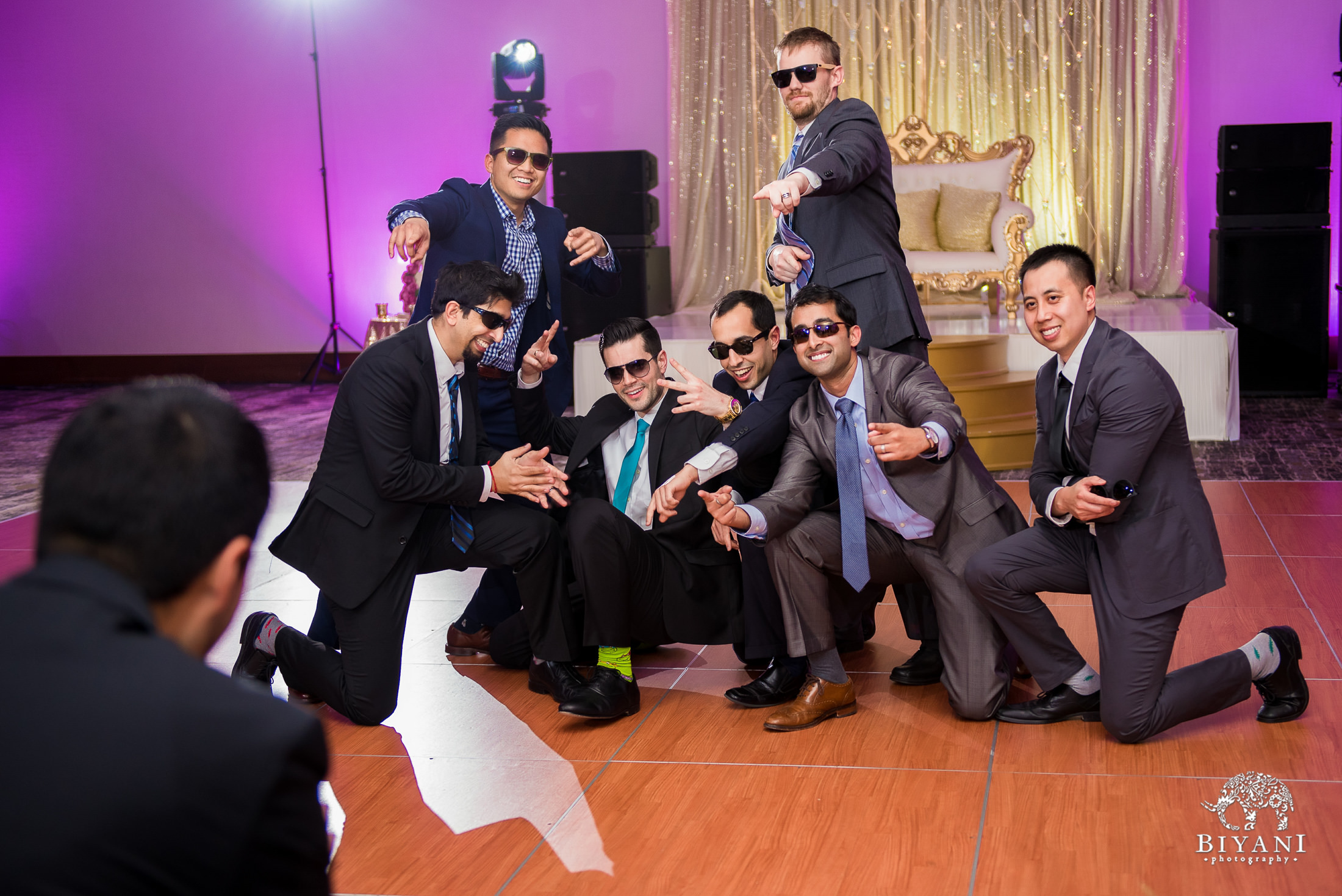 groomsmen posing after their dance on the reception dance floor