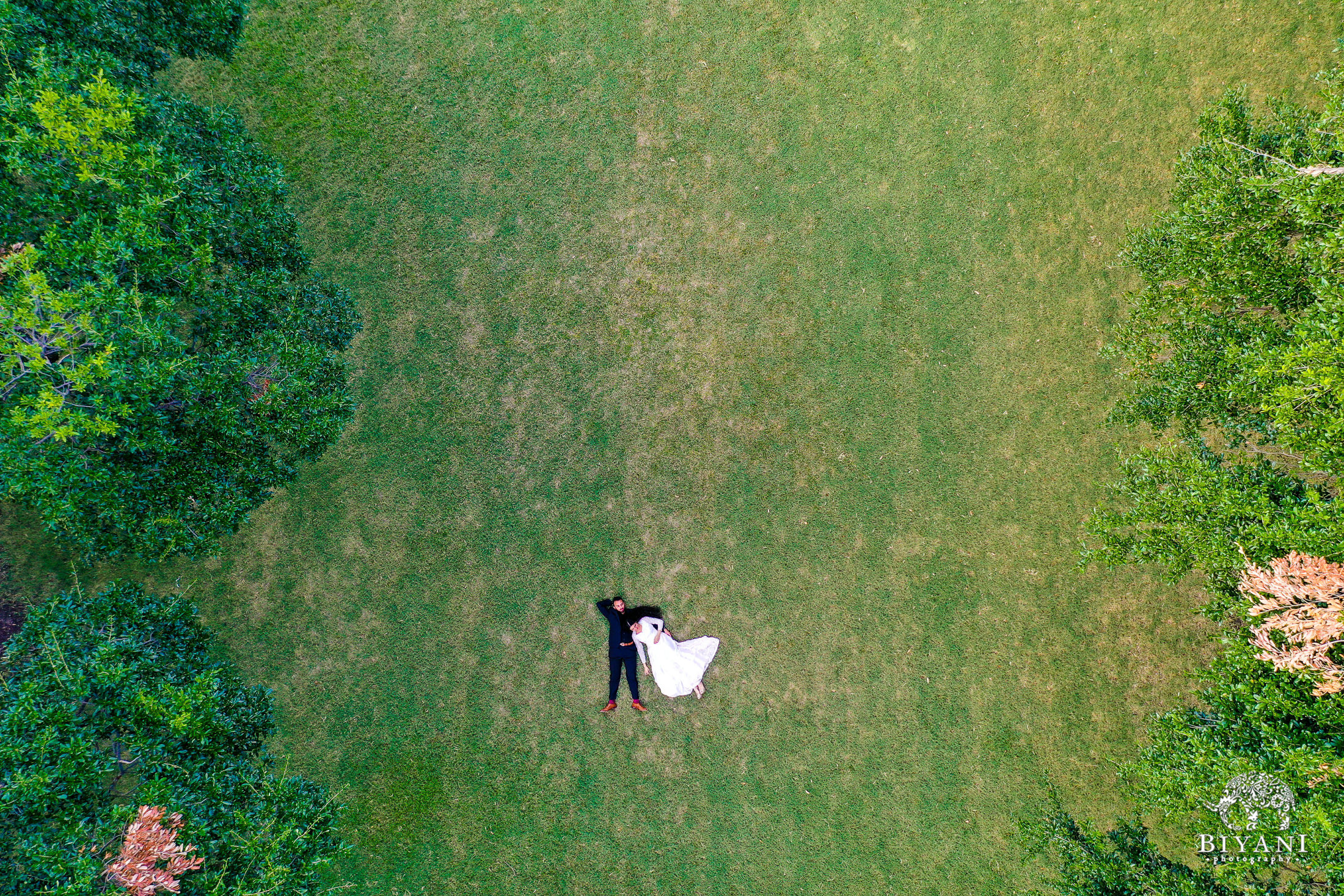 drone photography of couple laying on grass together