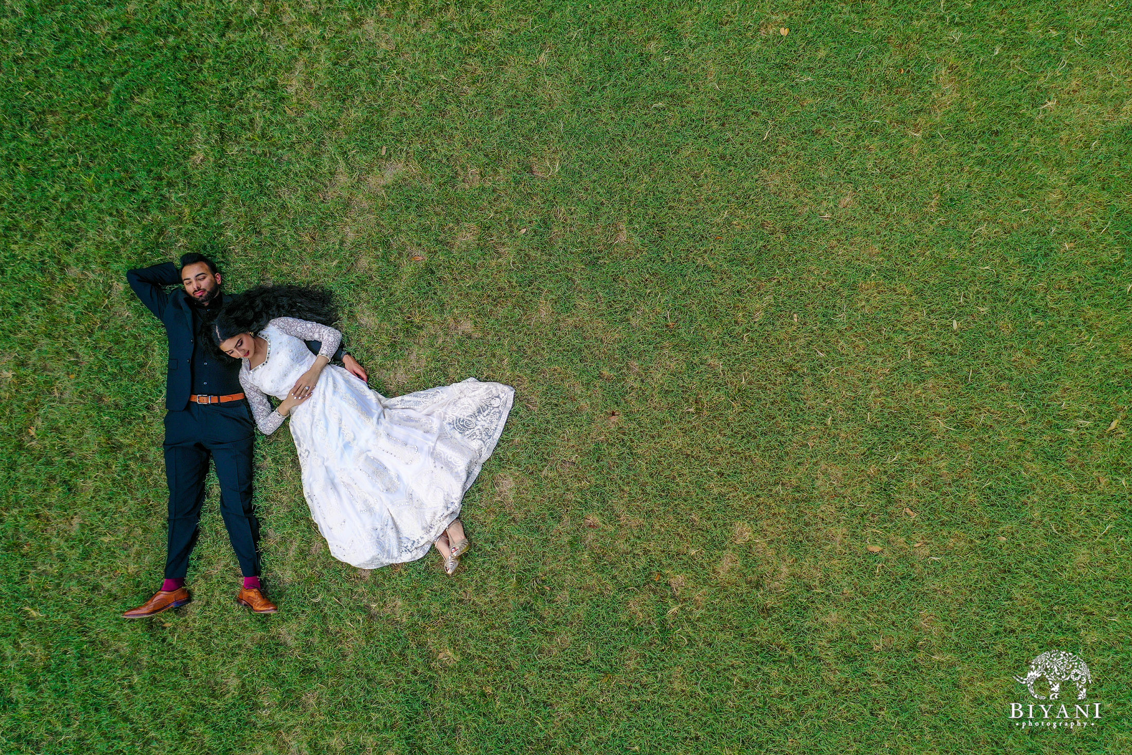 drone photo of bride laying on groom's chest in the grass