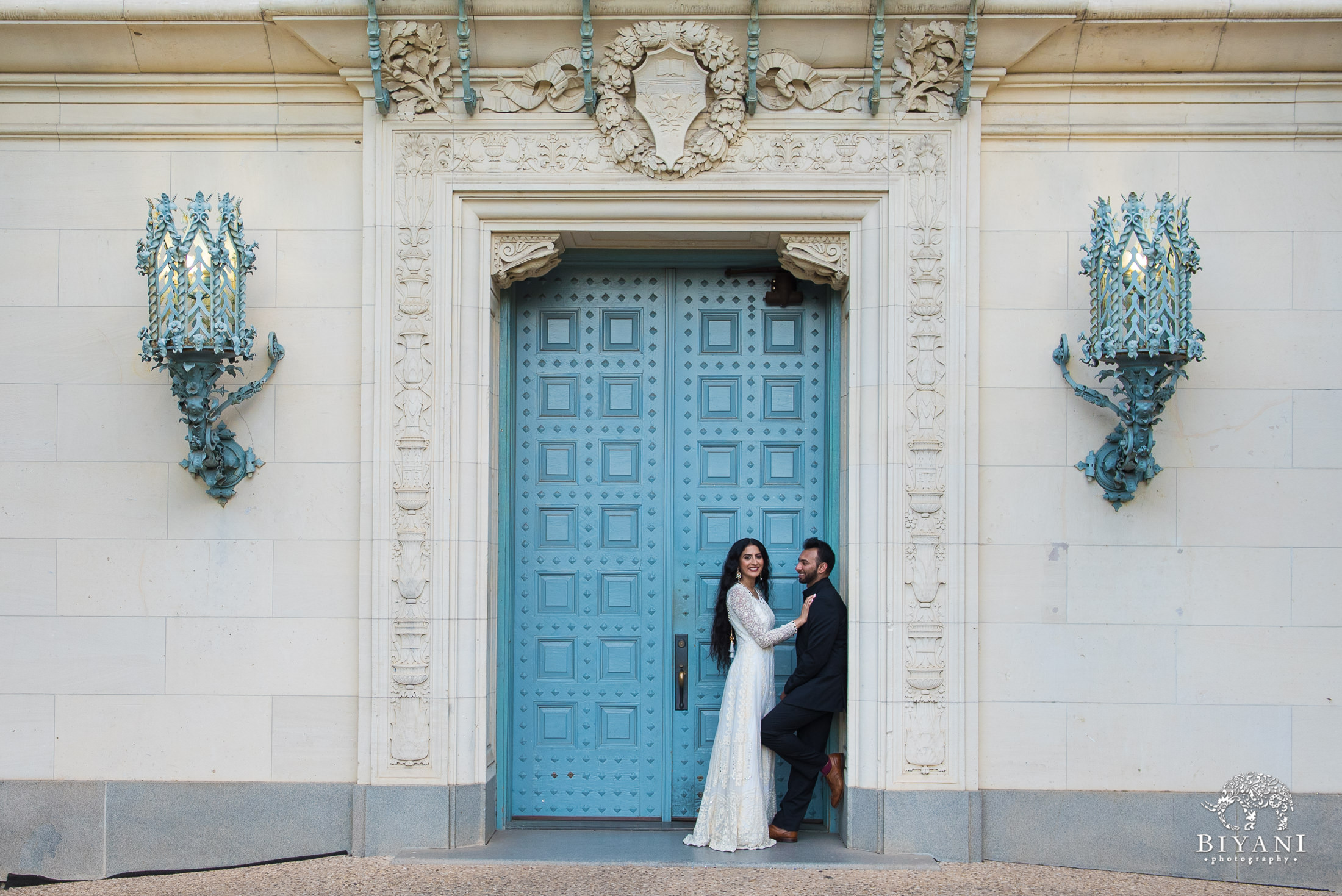 couple posing in front of blue door on building at University of Texas, Austin campus