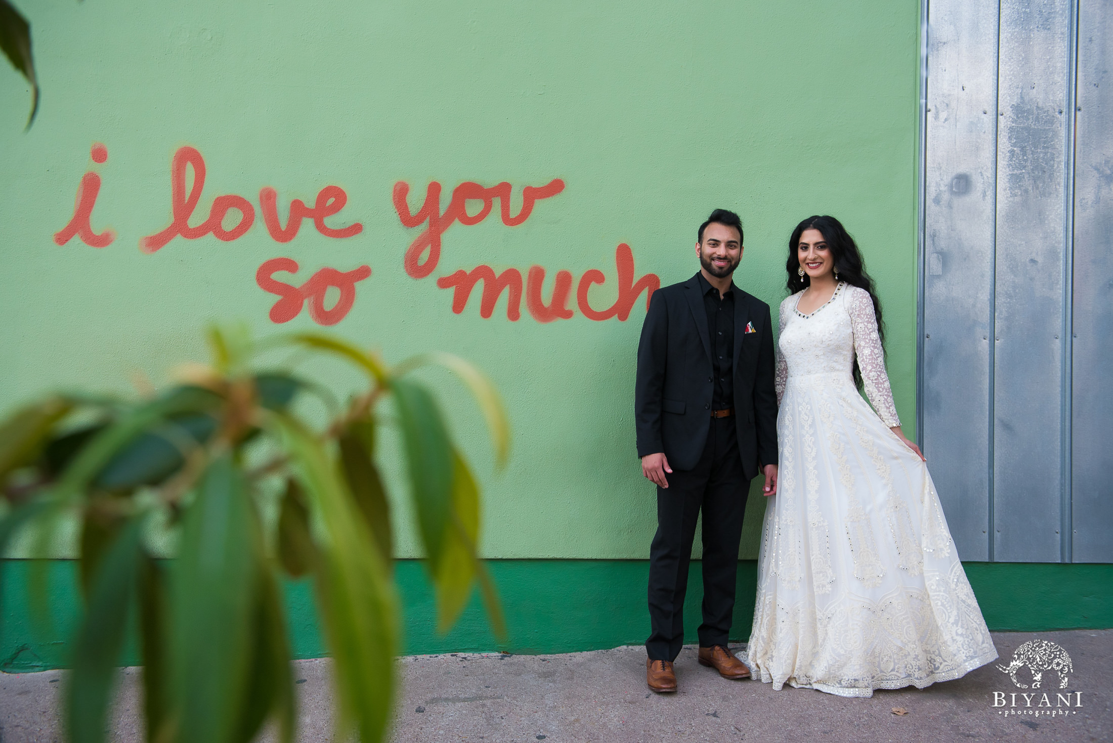 "couple poses in front of ""I love you"" mural in Austin, Texas"