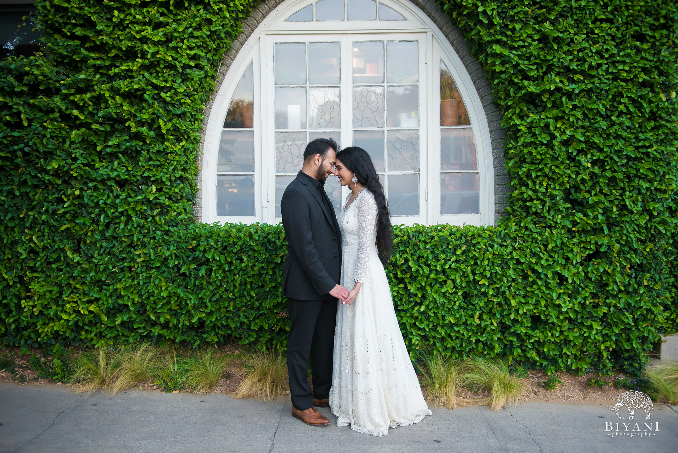 couple touching foreheads together in front of a vintage window with ivy growing around it