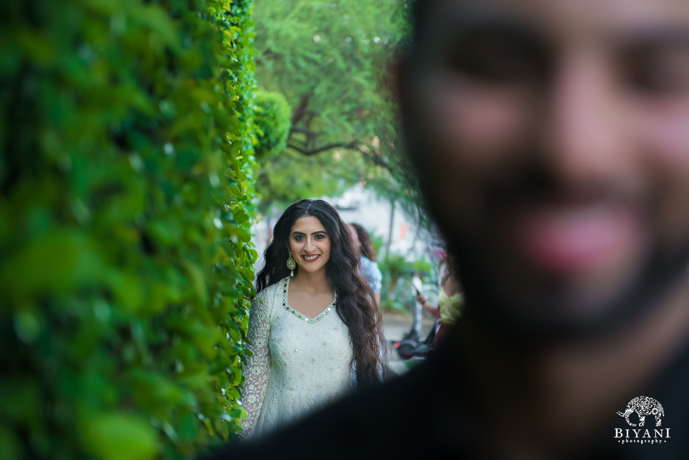 bride in focus sneaking up on groom out of focus from behind