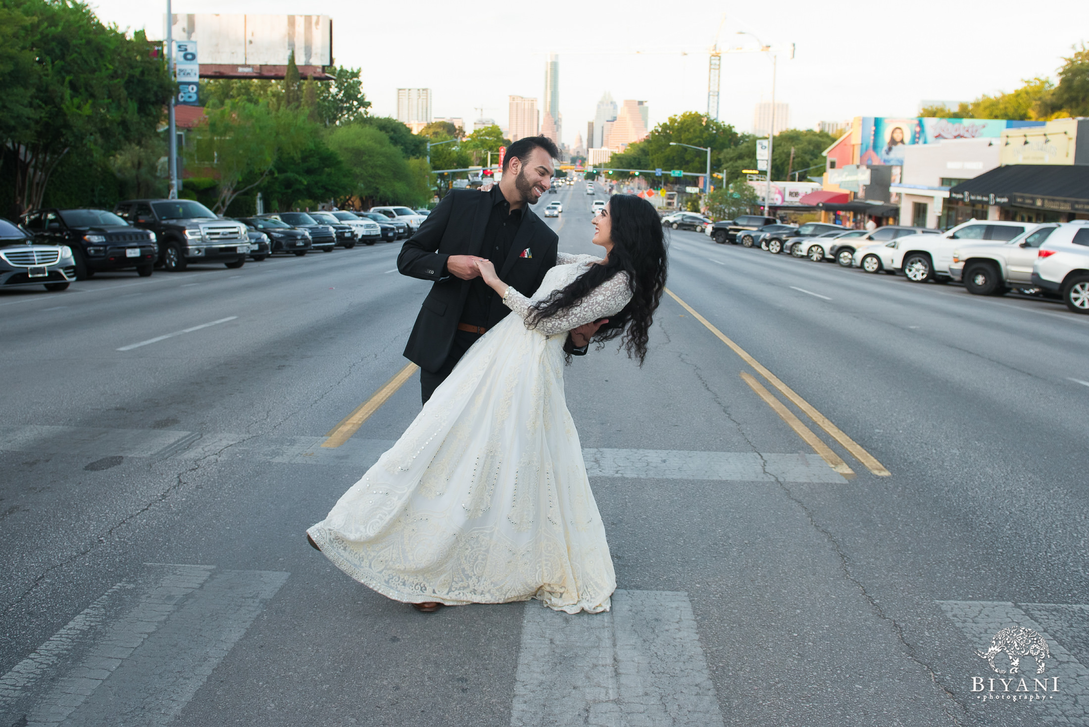 bride being dipped by groom in the middle of intersection with Austin city Capital in background