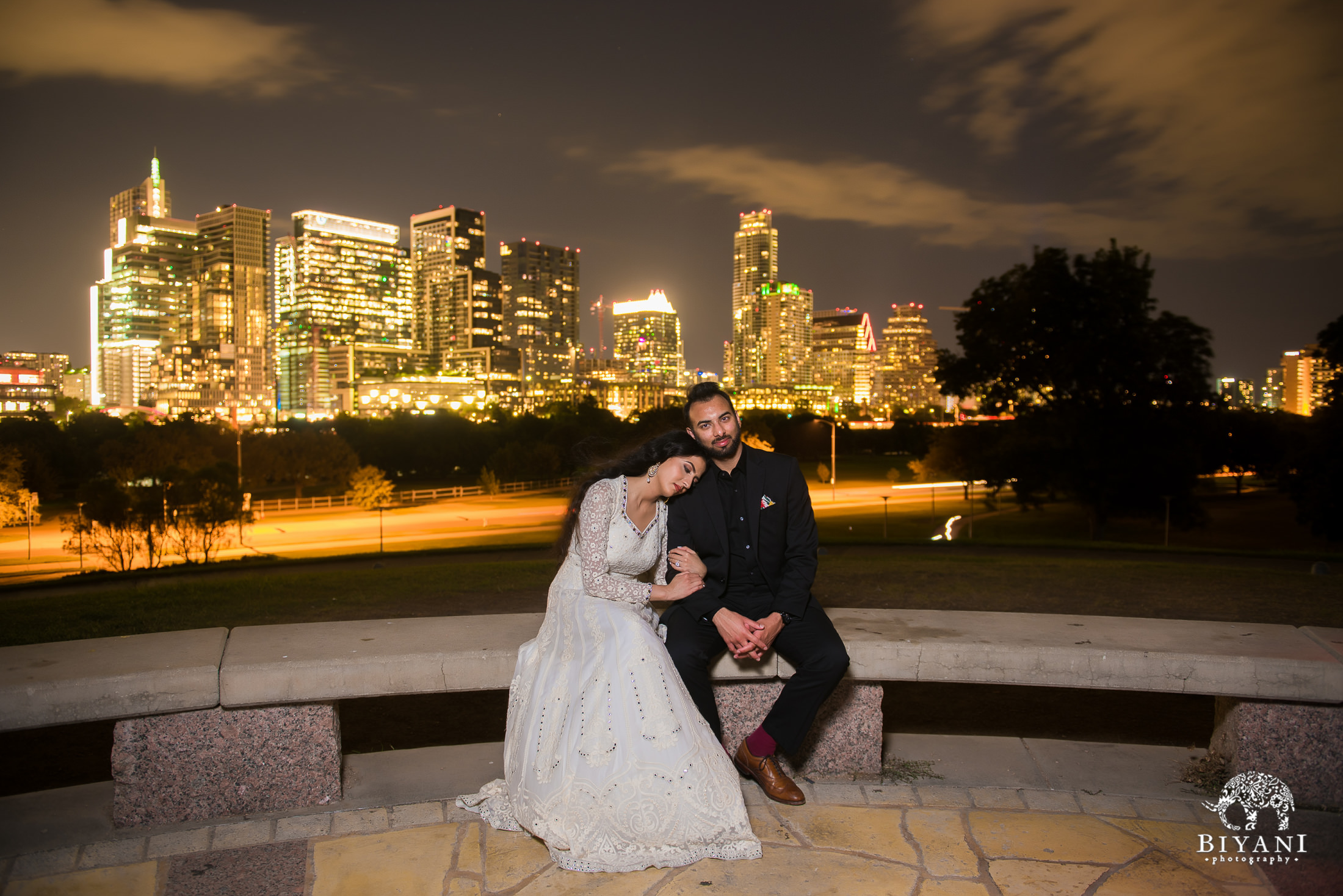 couple sitting on bench together in front of Austin city skyline during night