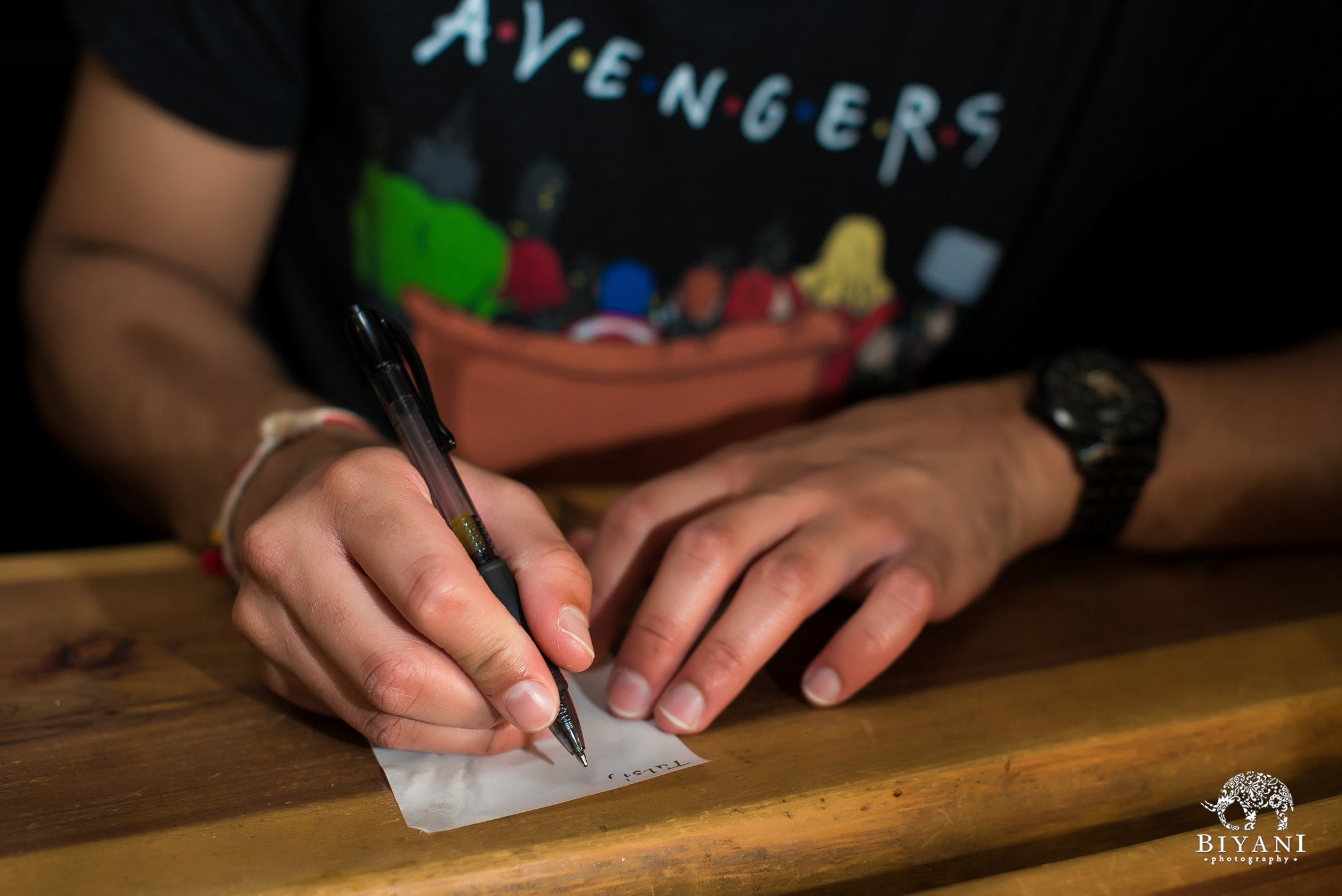 Groom writing secret love letter for bride at coffee shop wearing an Avengers t-shirt