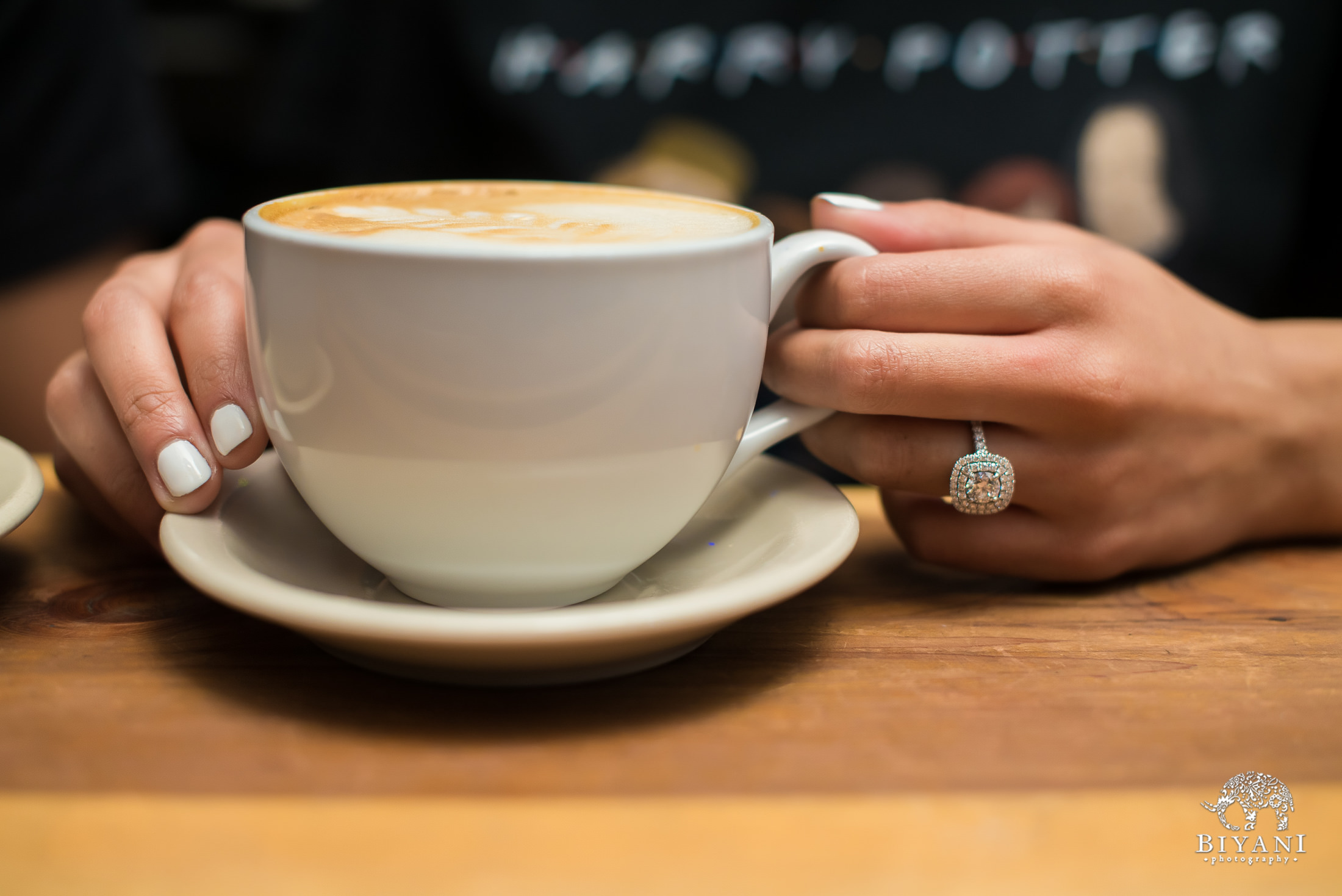 bride holding her cappuccino cup with engagement ring on her finger