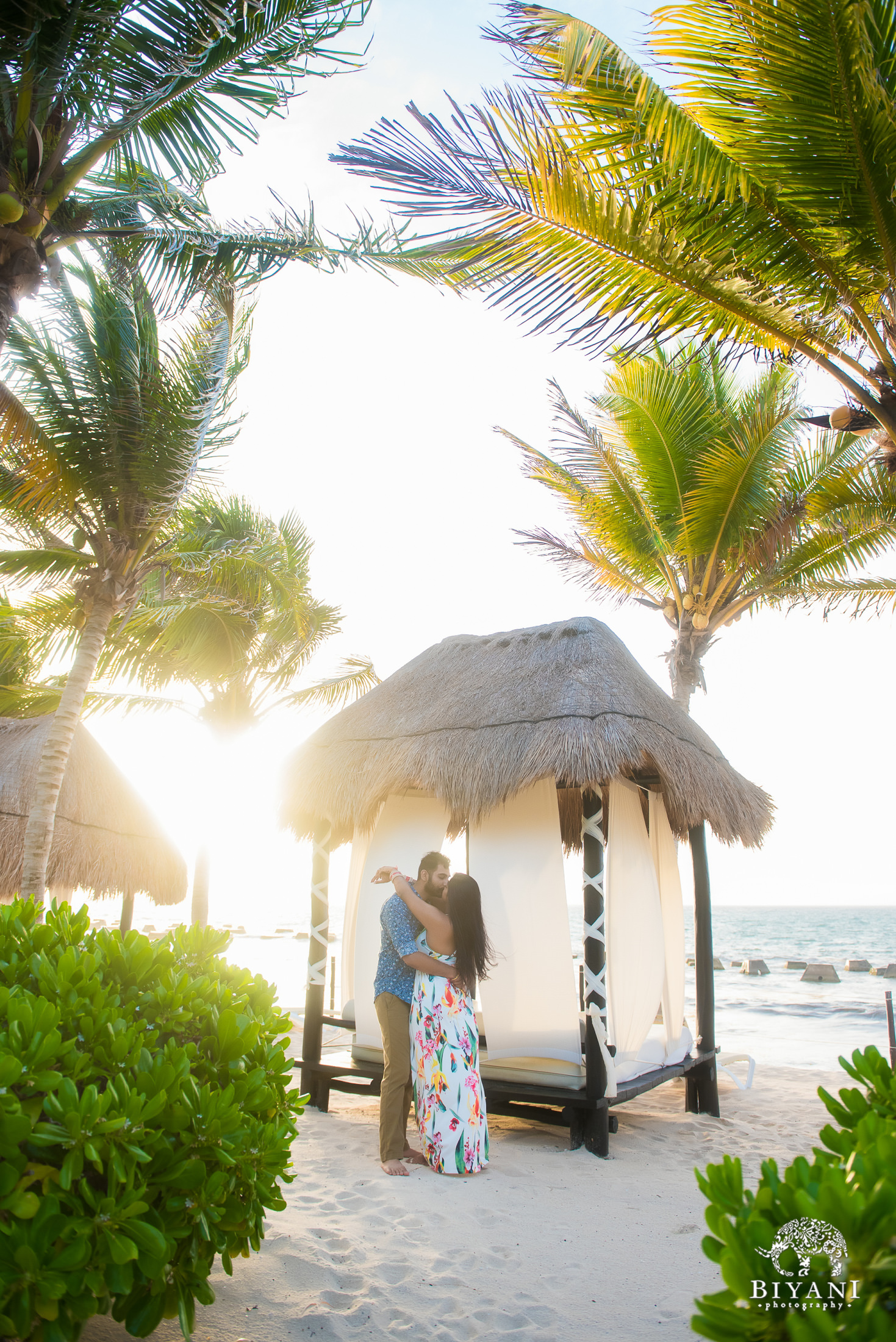 couple standing in front of a beach cabana during sunset in Mexico