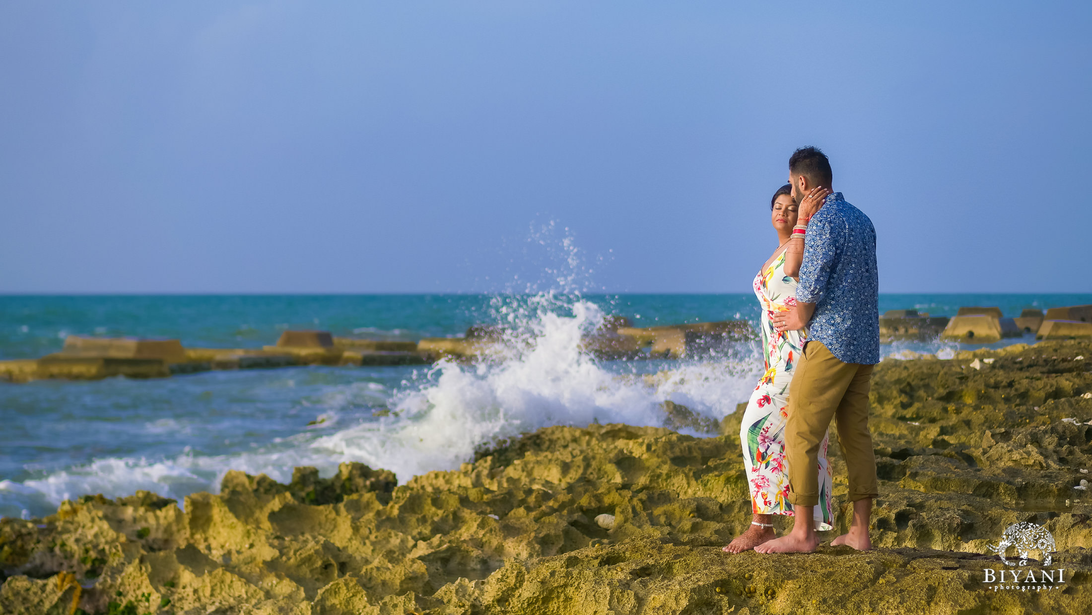 couple posing on rocks with ocean waves splashing in background in Mexico