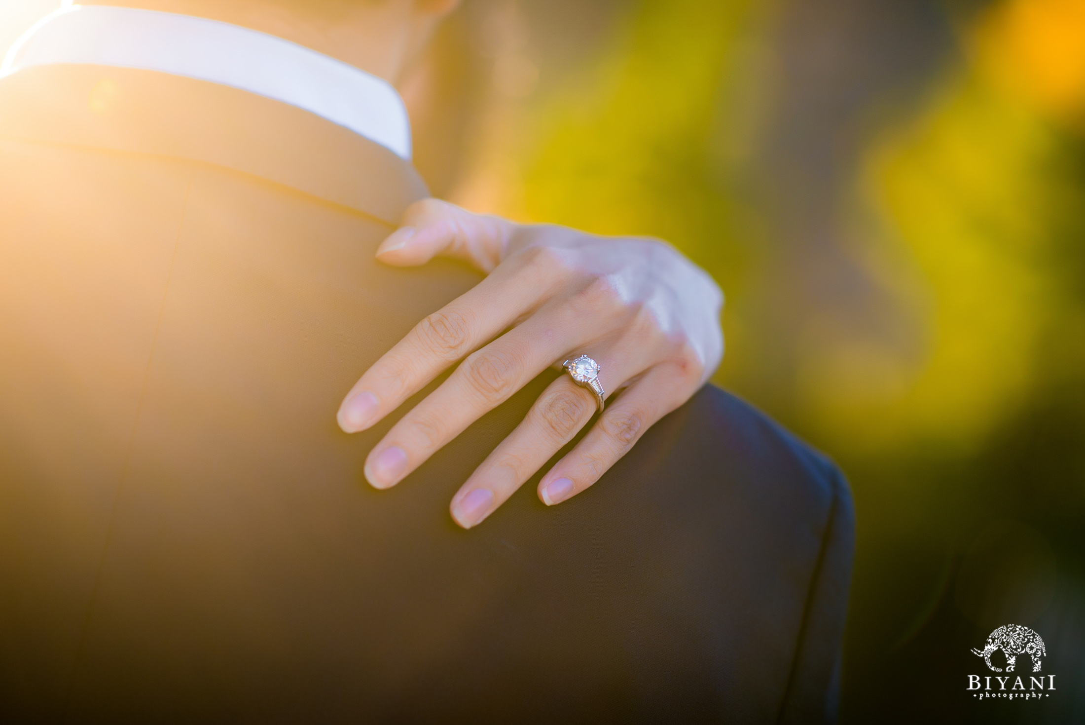 bride shows off engagement ring over grooms shoulder with sun flare