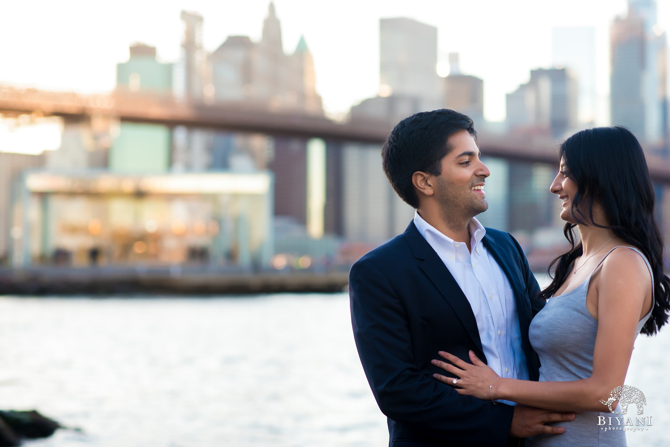 engagement shoot in front of Brooklyn Bridge in New York City with couple looking at each other