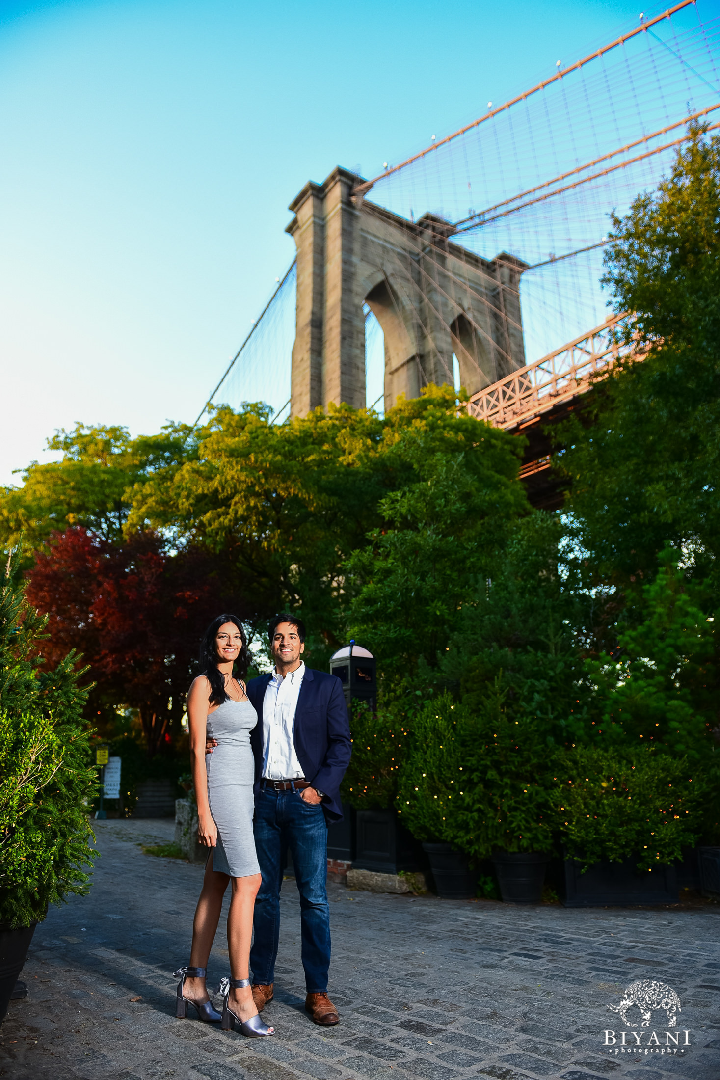 couple standing between green trees in front of Brooklyn Bridge in New York City