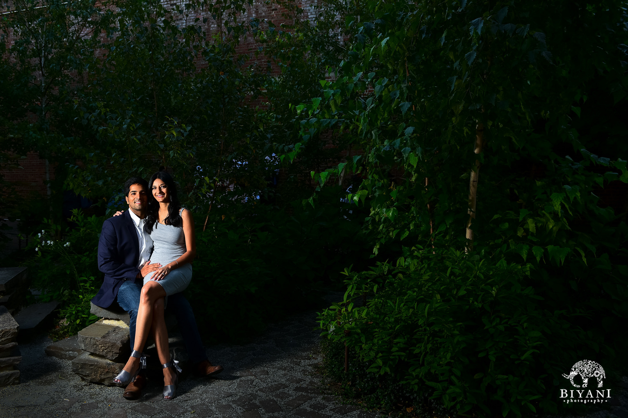 couple posing in green landscape in the middle of New York city streets