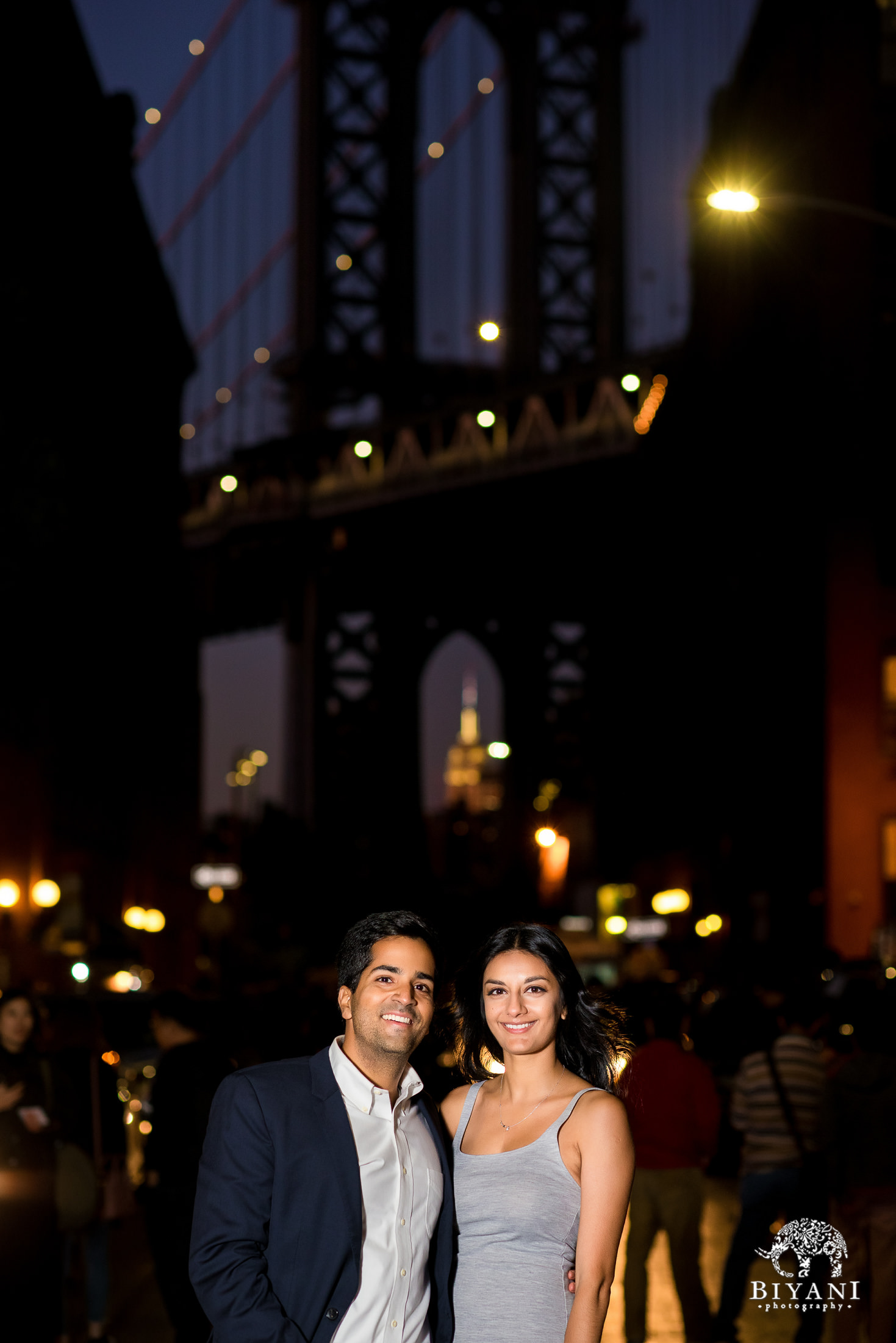 couple in front of Manhattan Bridge at night with city lights shining bright