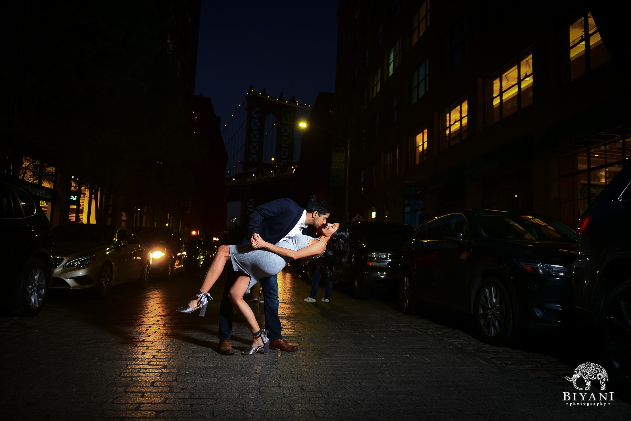 groom dips bride and leans in for a kiss in front of Manhattan Bridge at night
