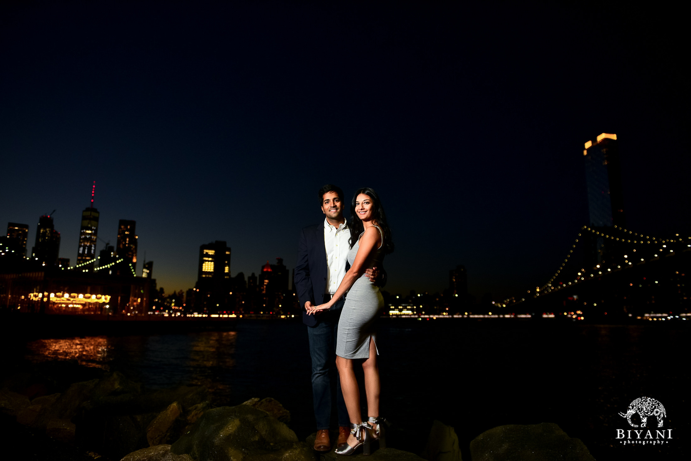 couple standing on rocks in front of New York city Skyline at night with city lights shining behind them