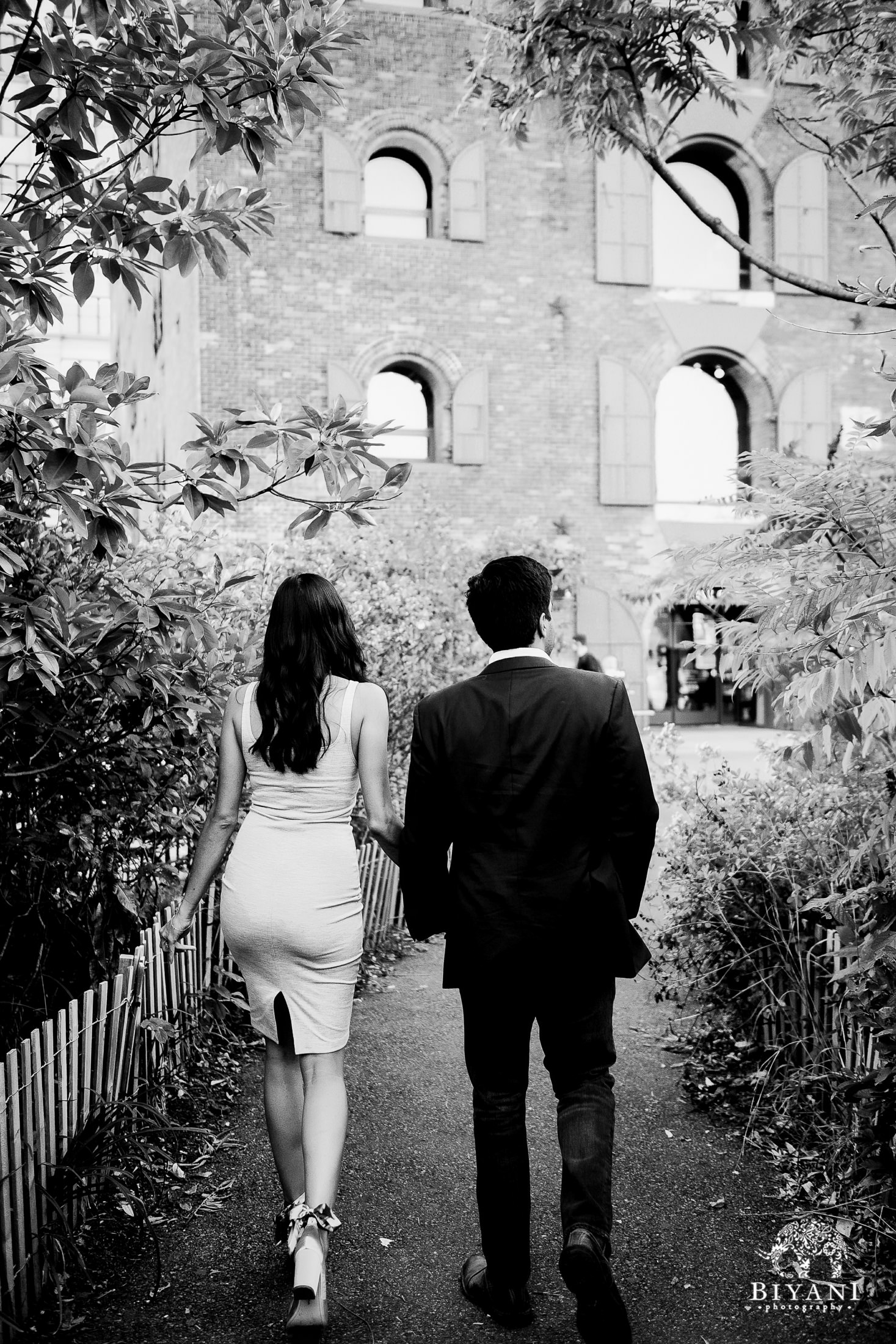 couple walking towards building with arched windows while holding hands