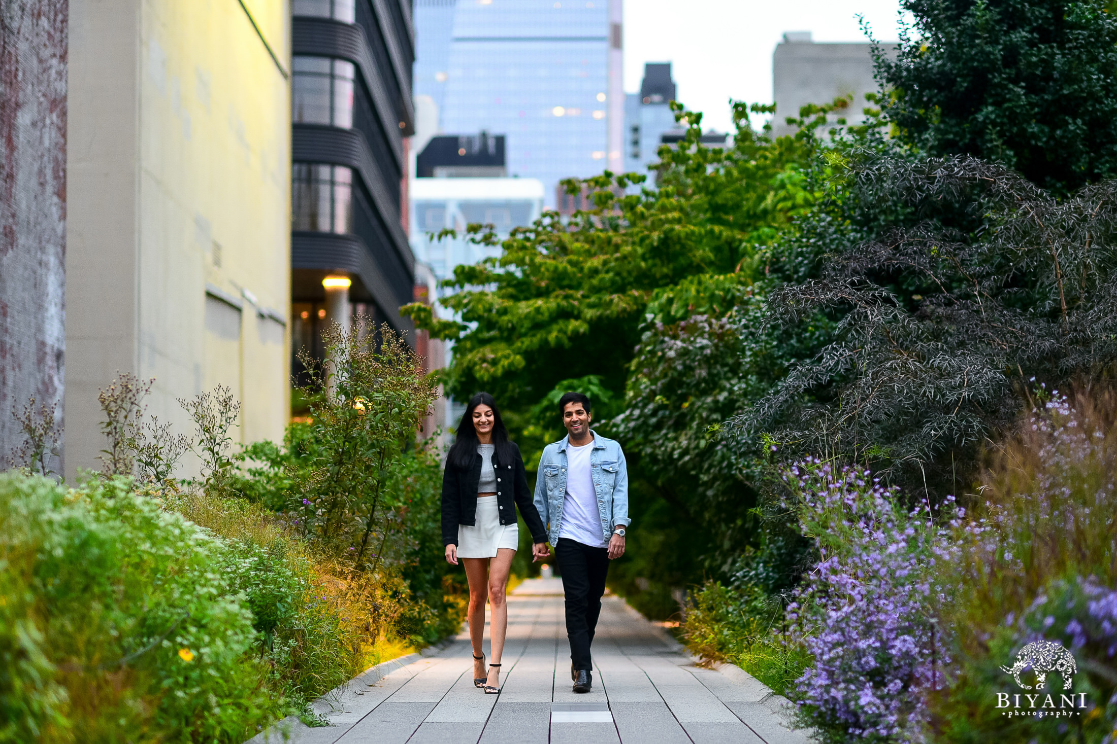 couple holding hands walking towards camera