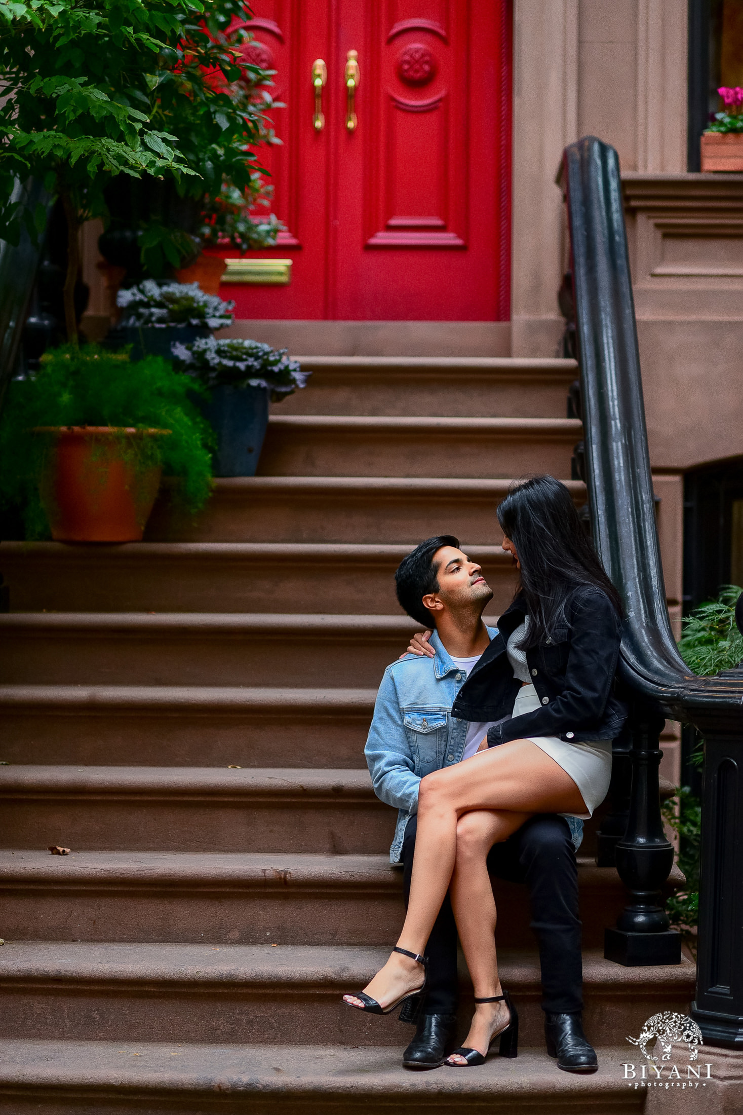 bride sitting on grooms lap in front of a New York city house with a red door