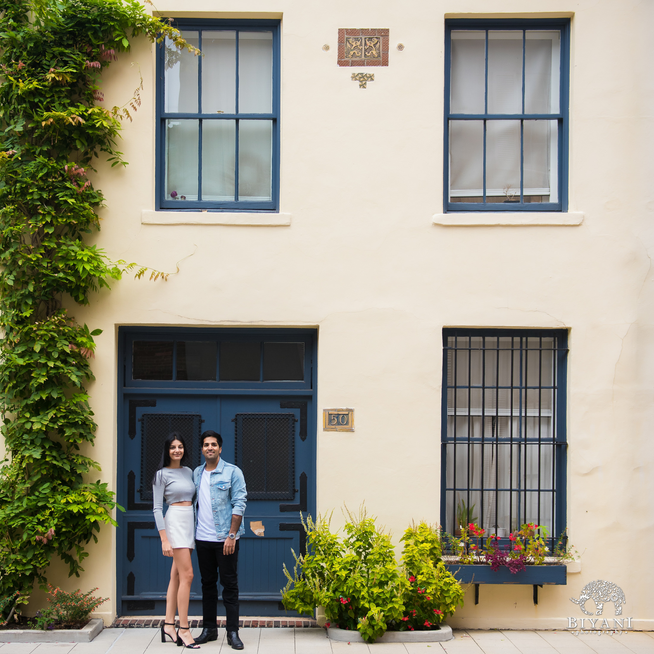 couple standing in front of a home with Ivy running down the wall
