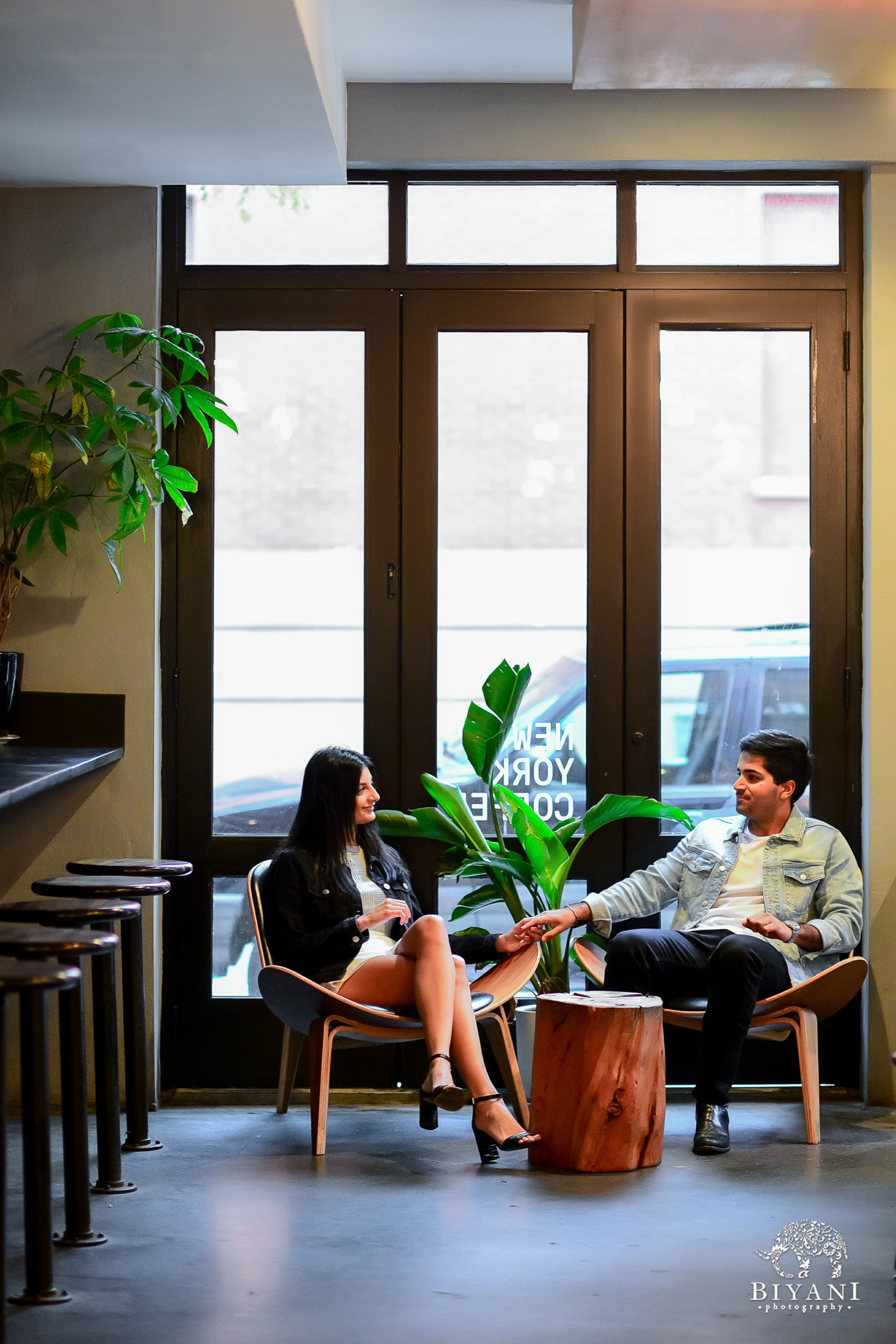 couple holding hands while sitting down at a coffee shop in New York City