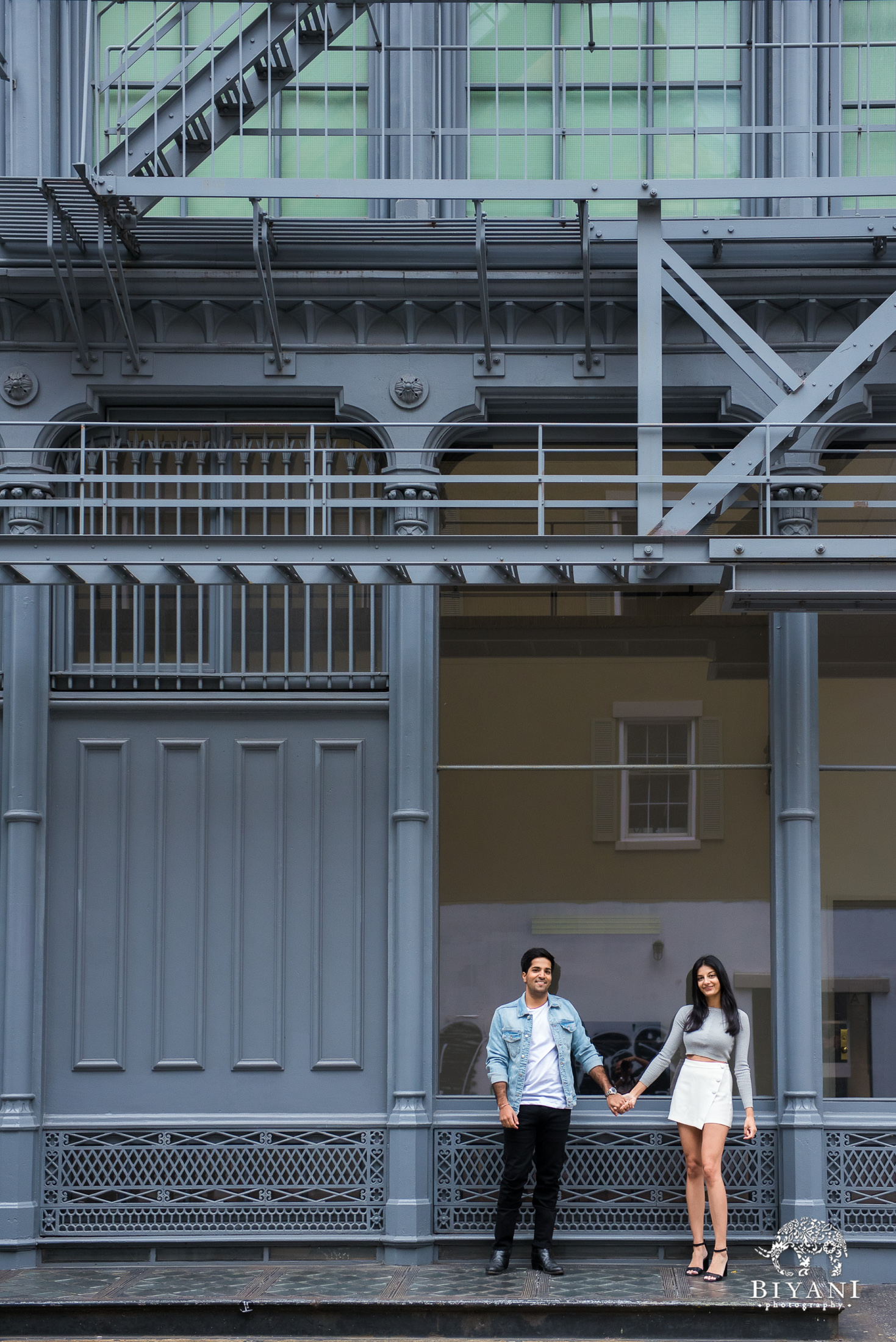 couple standing in front of a blue building