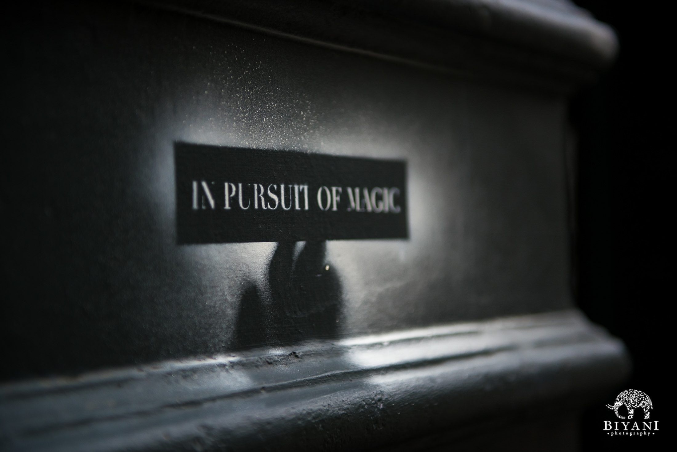 """In Pursuit of Magic"" sign in black and white"